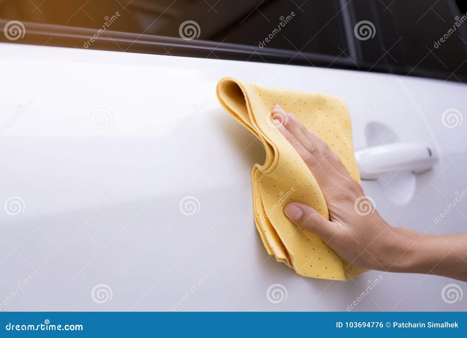 Esta imagem é uma imagem de limpar o carro com um pano amarelo do microfiber pelas mãos