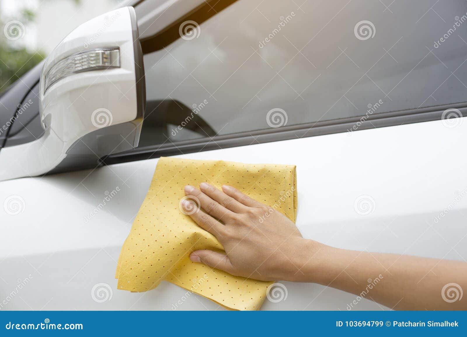 Esta imagen es una imagen de limpiar el coche con un paño amarillo de la microfibra al lado de las manos