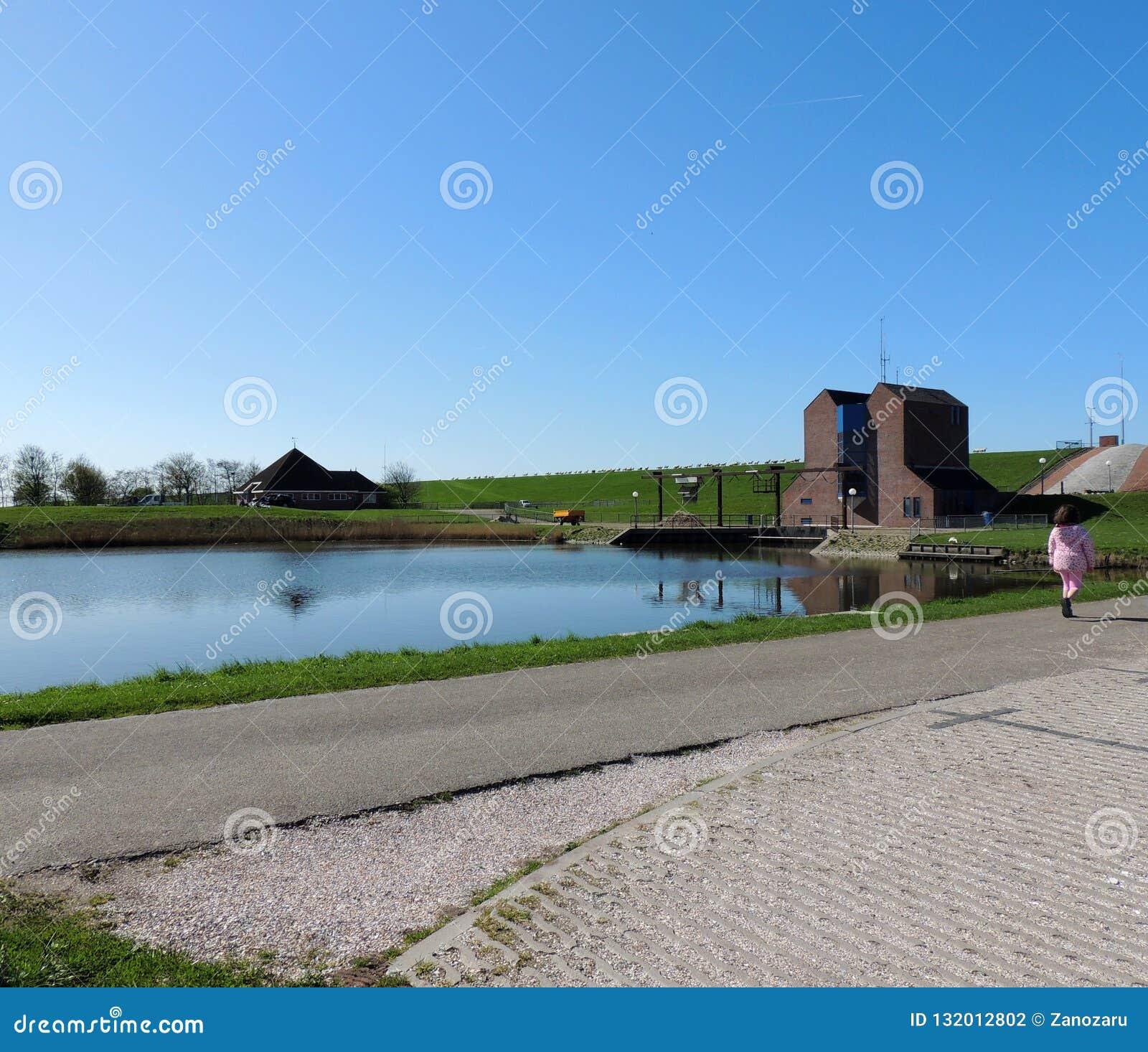 Estación de bombeo Nordpolderzijl Noordpolderzijl en la provincia de Groninga, los Países Bajos Presa en el Mar del Norte