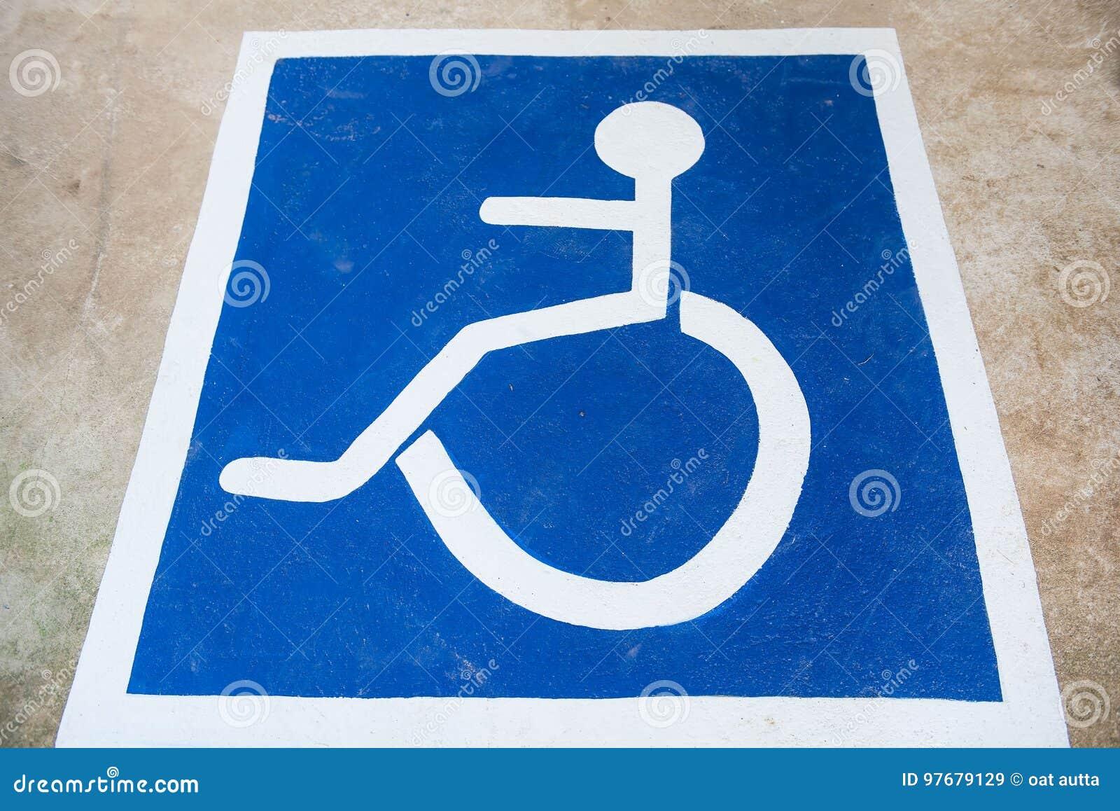 Estacionamiento blanco y azul del coche del símbolo de la desventaja de discapacitado en el piso