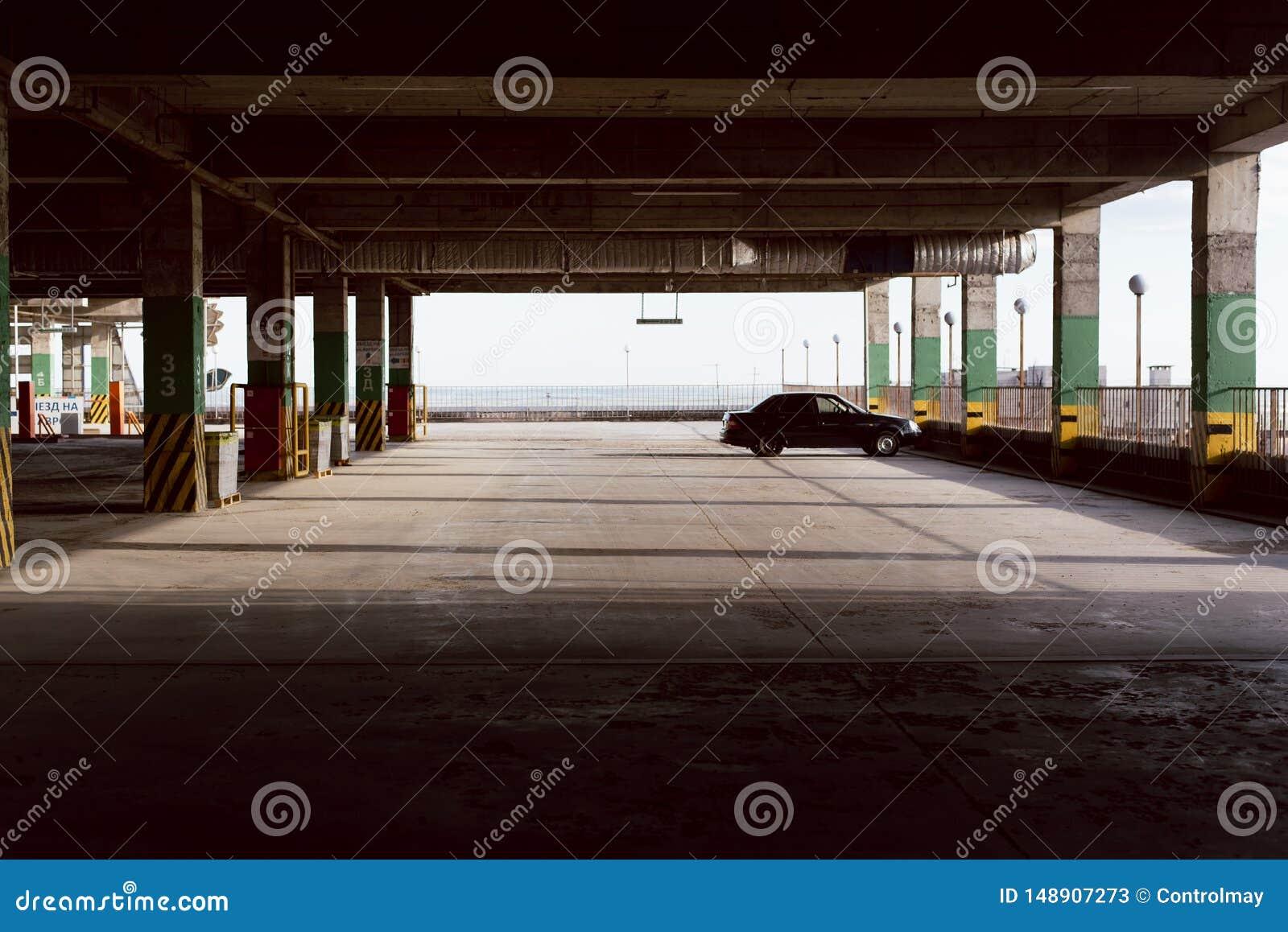 Estacionamiento vac?o Un coche en el espacio que parquea