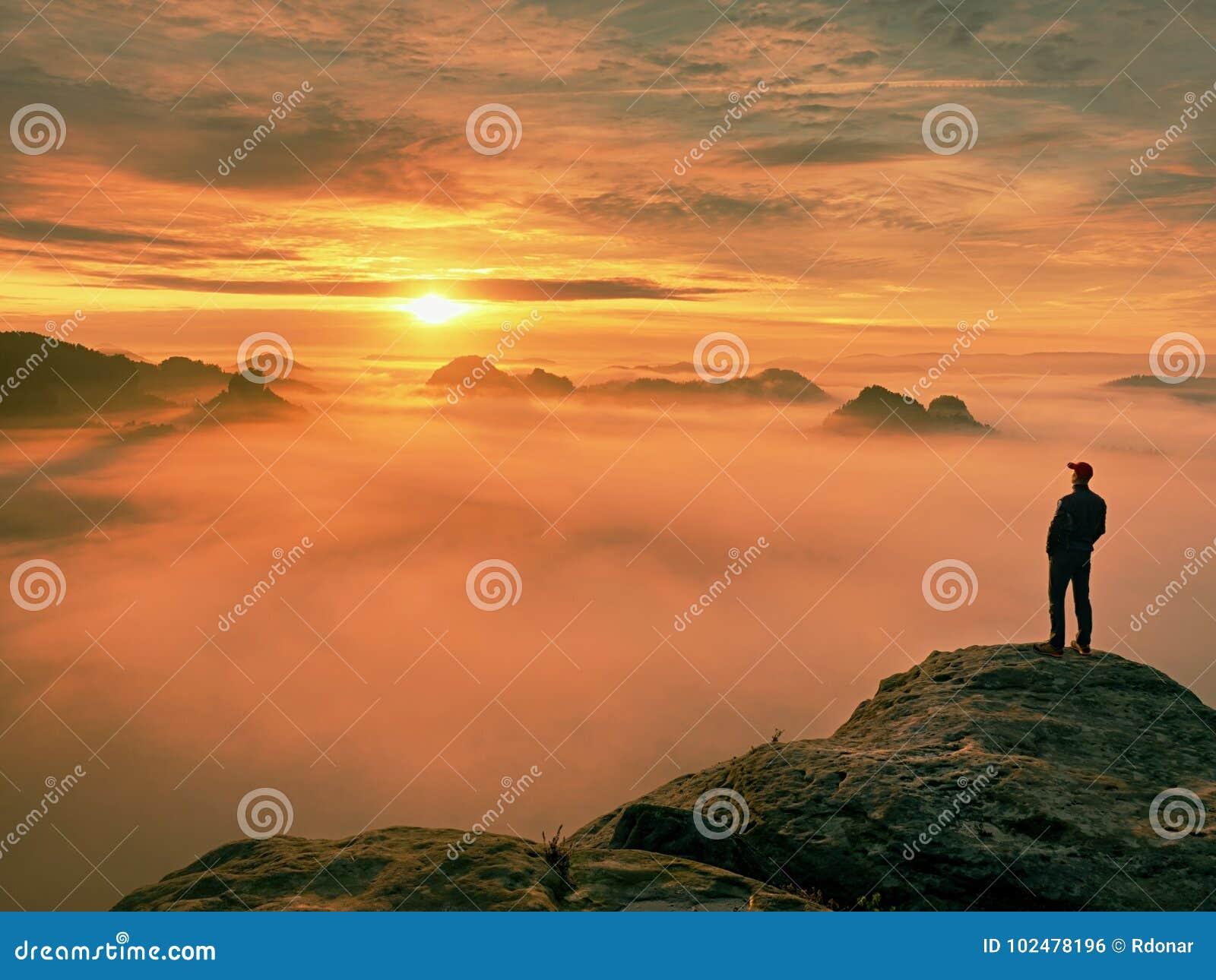Estada da silhueta do homem no pico afiado da rocha Satisfaça o caminhante apreciam a vista Homem alto no penhasco rochoso