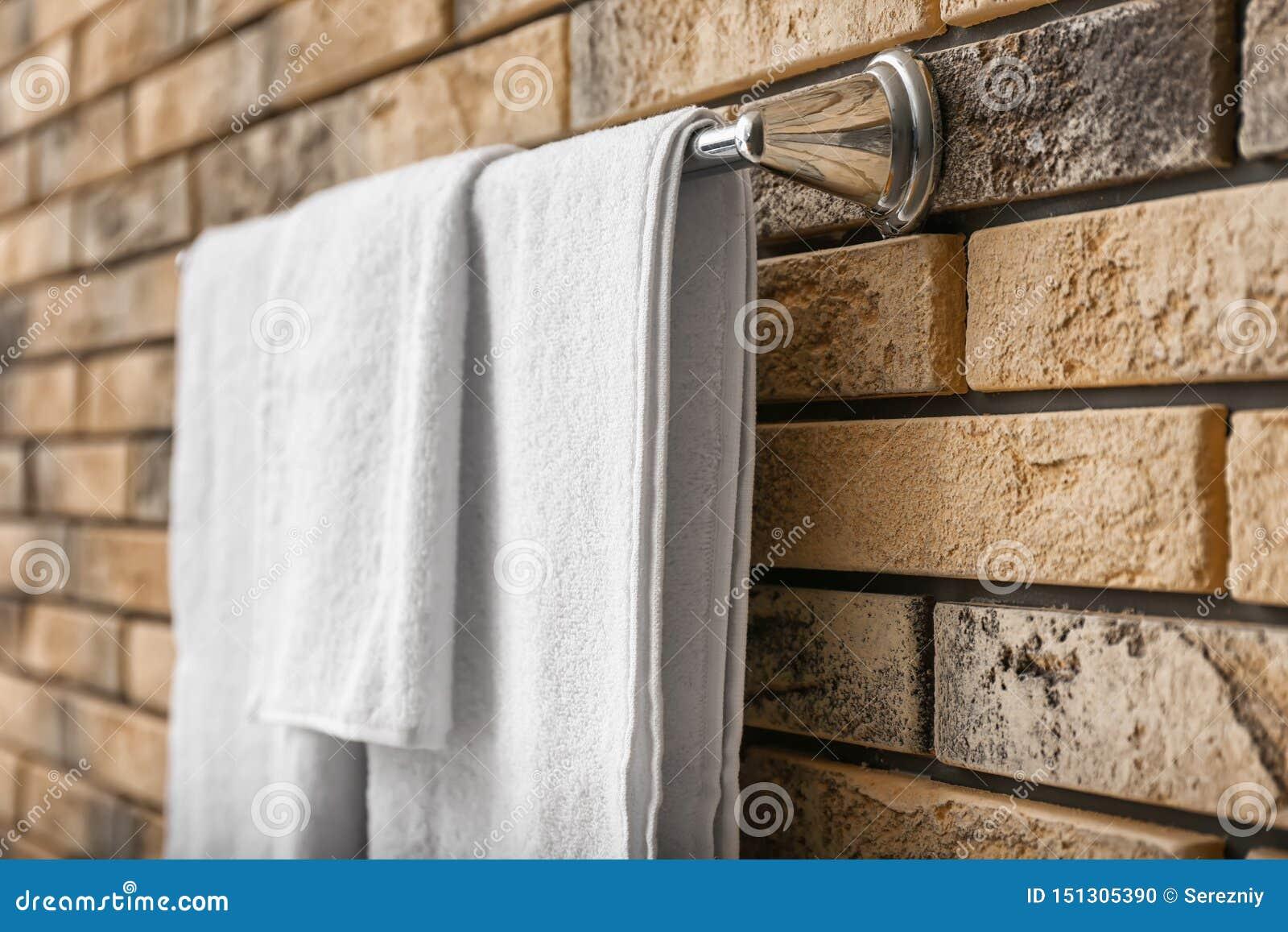 Estante con las toallas de Terry blancas en la pared de ladrillo, primer