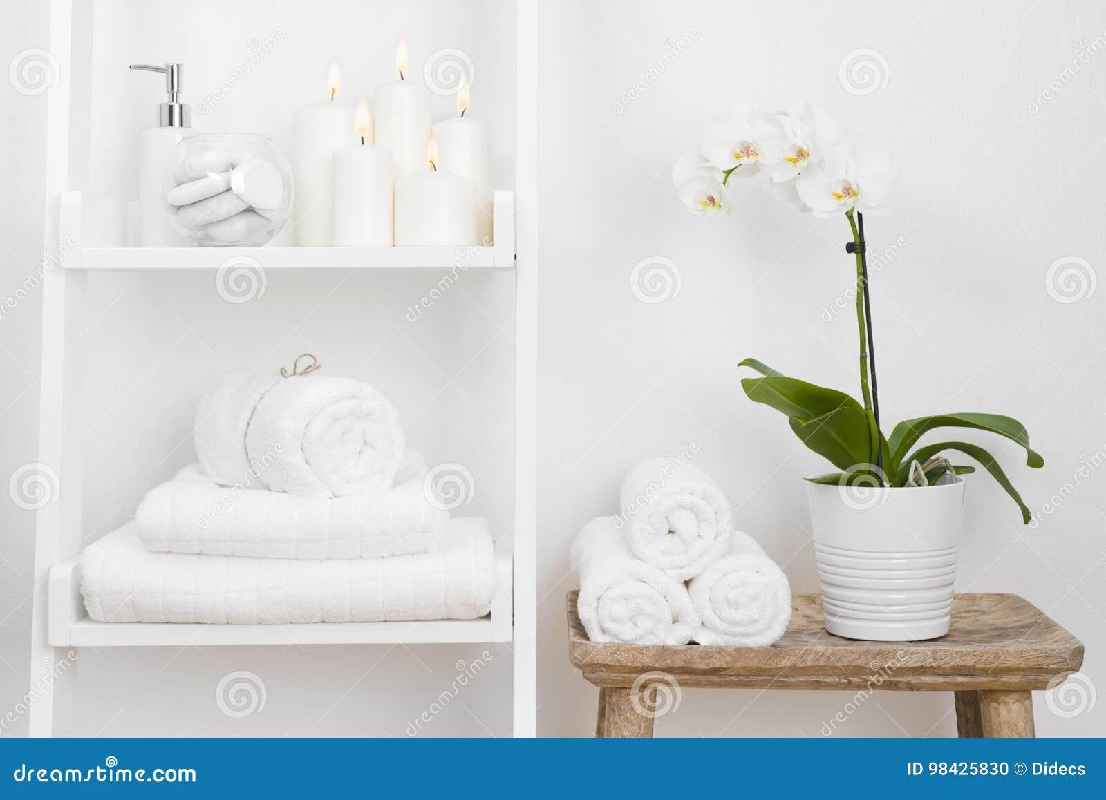 Estante con las toallas limpias, velas, maceta en la tabla de madera del cuarto de baño