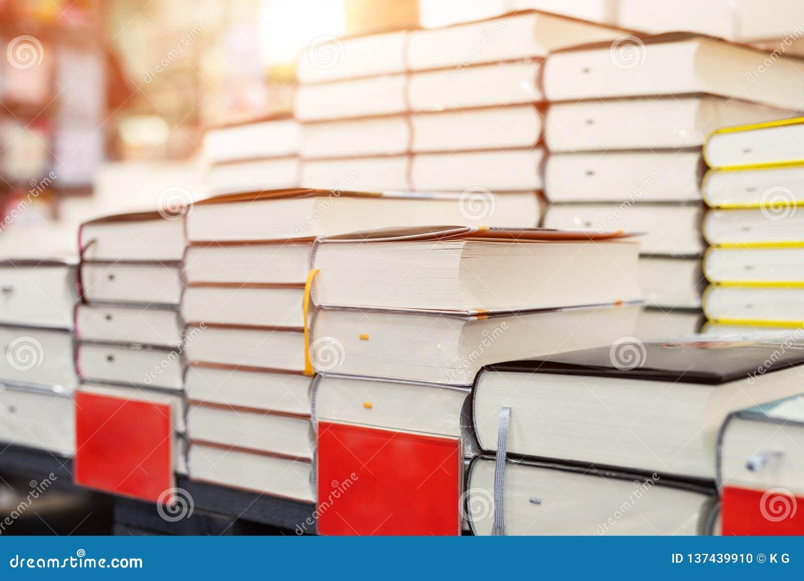 Estante de la librería con la pila de nuevos libros con la placa vacía roja Nuevas llegadas en la librería Presentación del libro