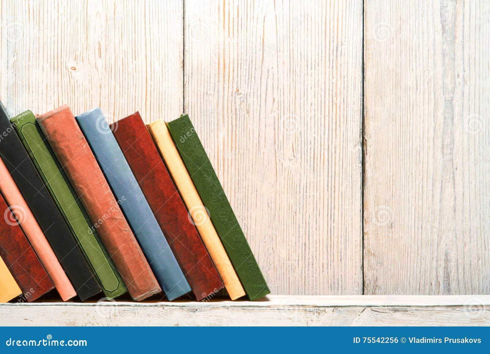 Estante de madera de los libros, viejas cubiertas de las espinas dorsales, pared de madera blanca