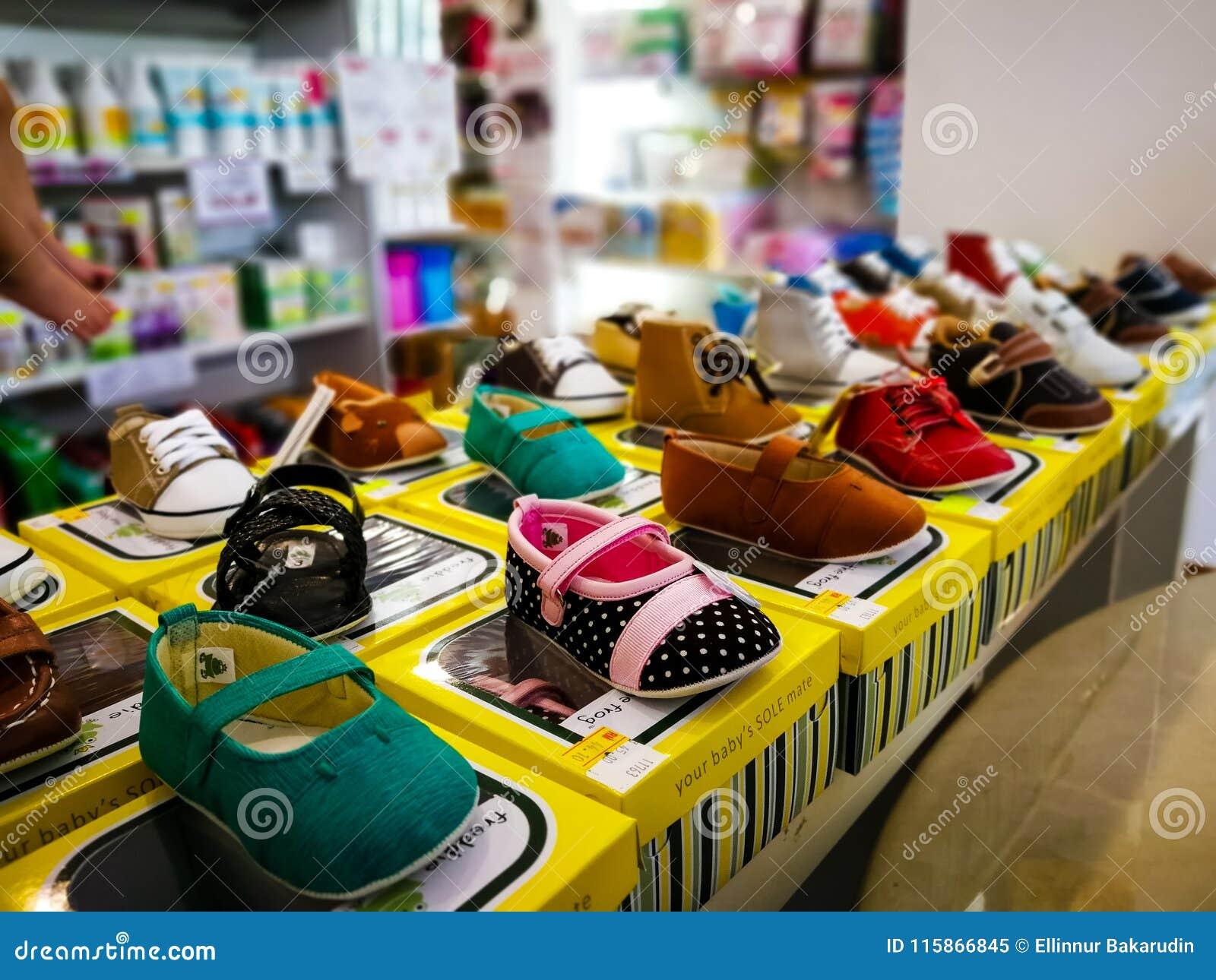 b8aa70ff335 Estantes con el surtido de zapatos de bebé en la tienda para la venta