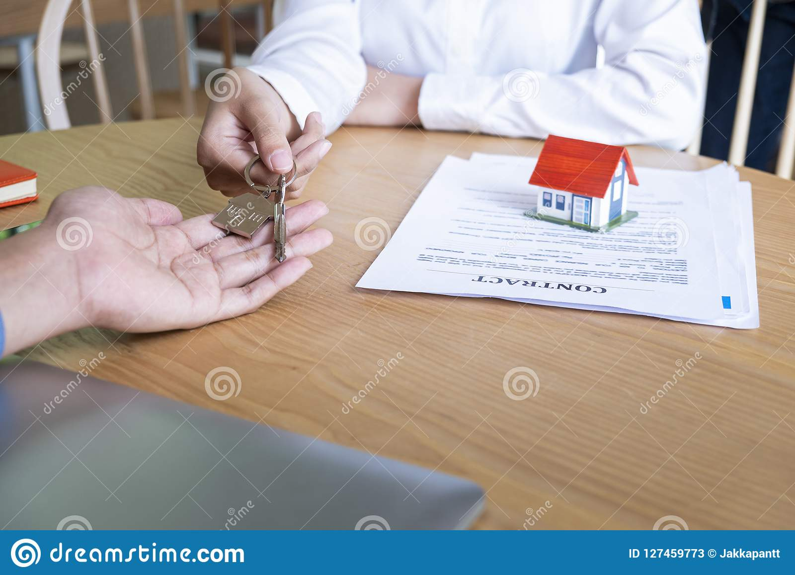 Estate agent giving house keys to owner and sign agreement in office
