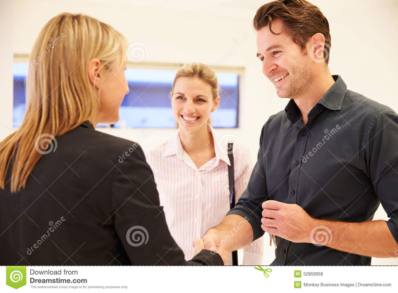Estate agent shaking hands with clients in empty office for Com agent immobilier