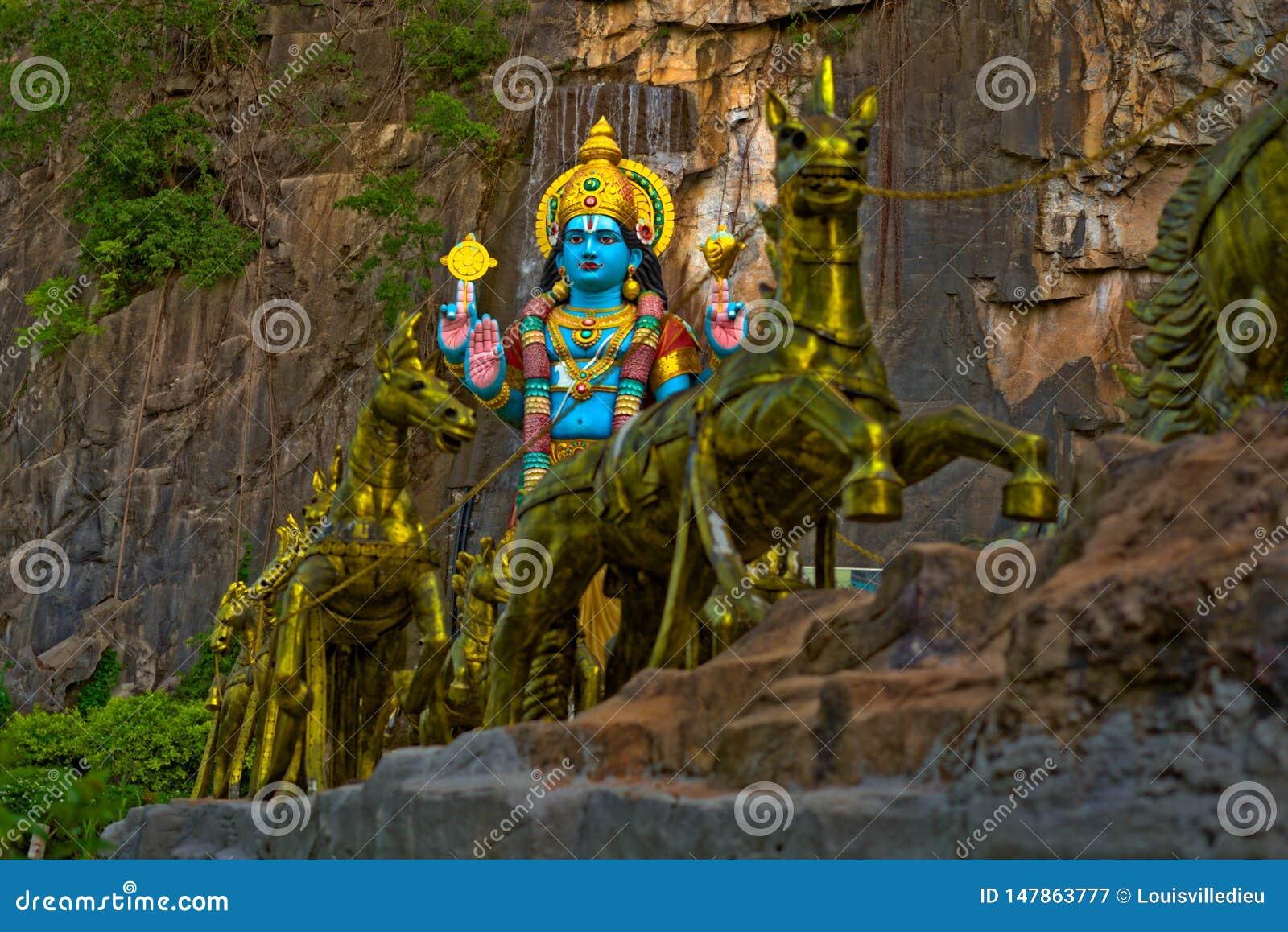 Estatua de dios de Krishna Hindu con los caballos de oro en las cuevas Gombak de Batu