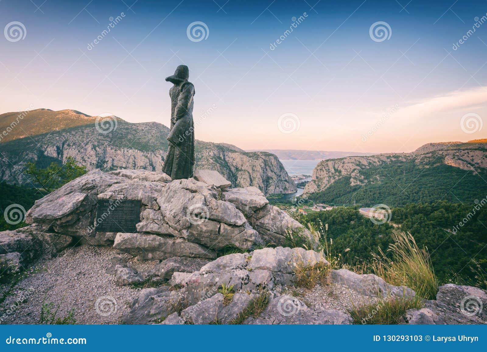 Estatua de Mila Gojsalic legendaria encima de una montaña rocosa cerca de Omis, Dalmacia, Croacia