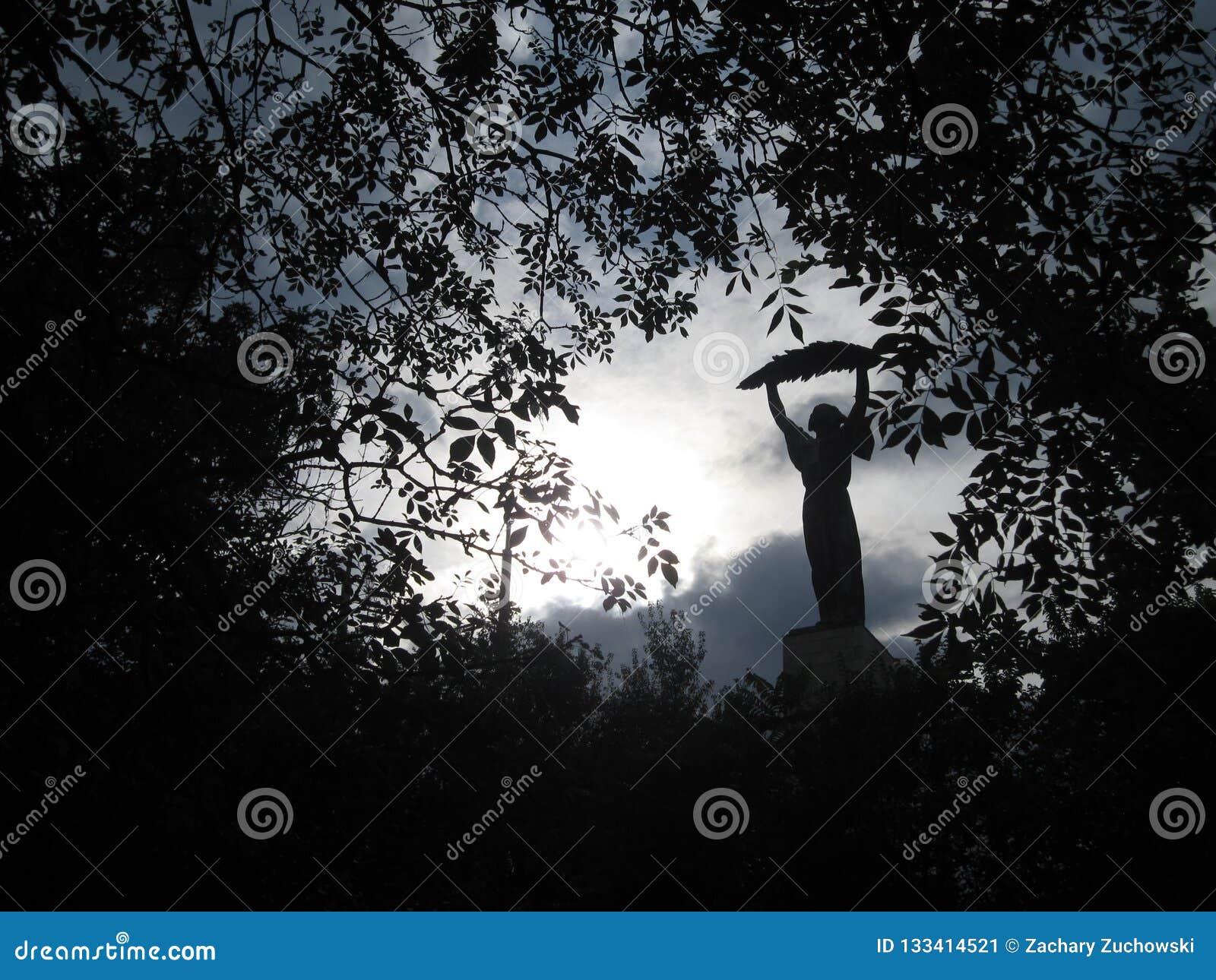 Estatua de una señora que sostiene una hoja entre las hojas