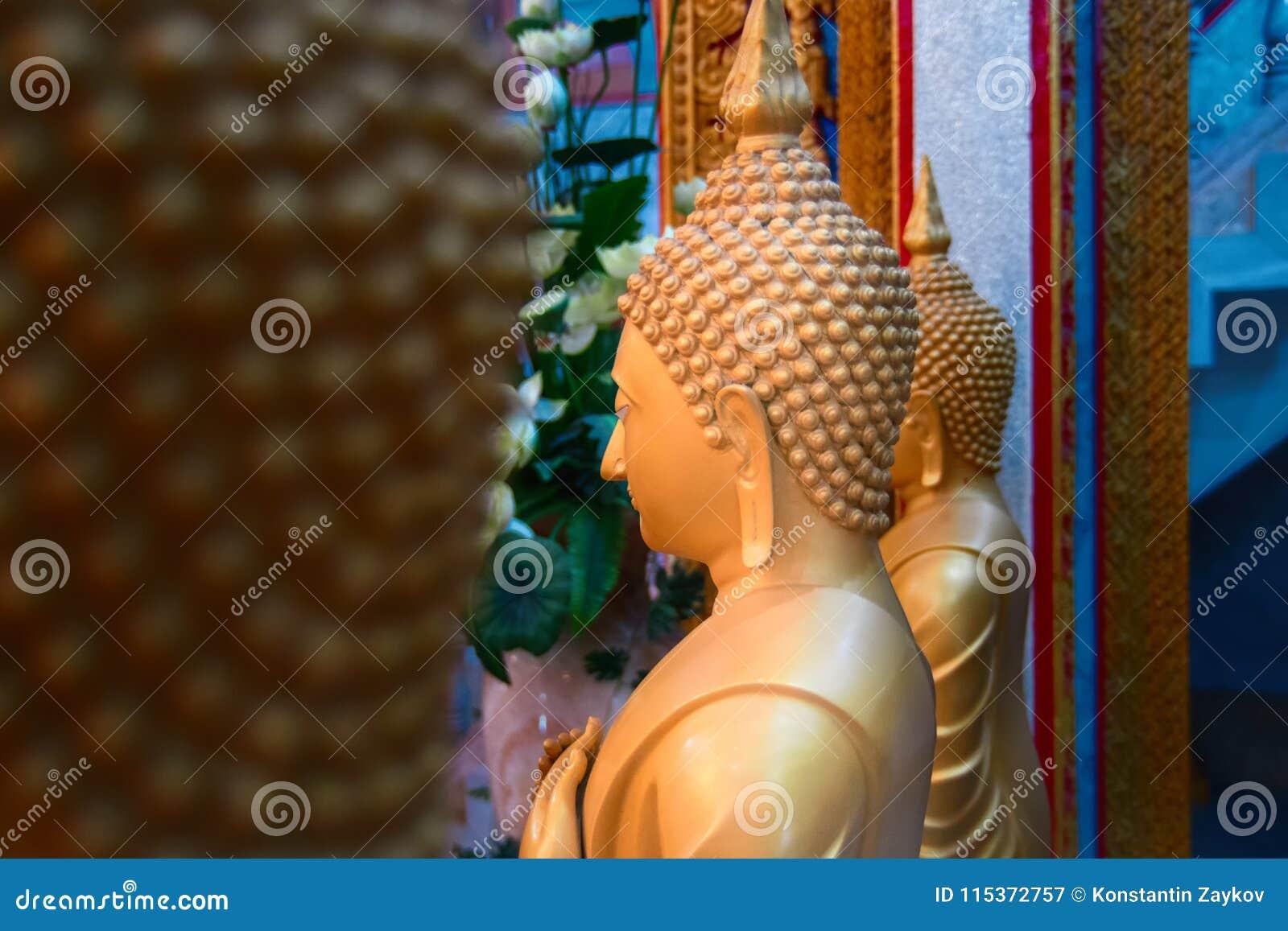 Estatuas de la cera de la vista lateral de monjes budistas en el templo Figuras de oro grandes Copie el espacio