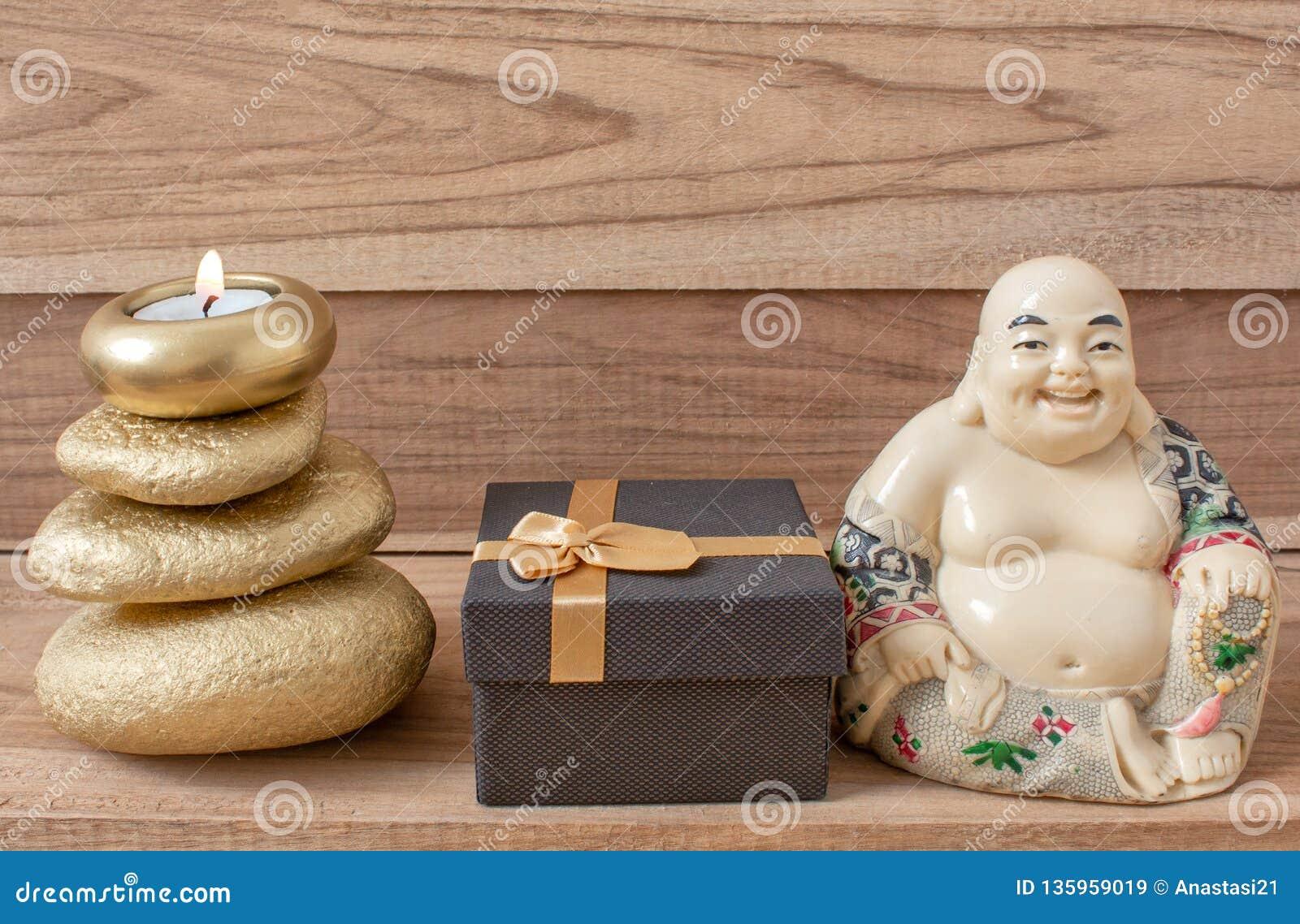 Estatueta de uma Buda de riso com pedras e uma vela, e uma caixa de presente, em um fundo de madeira, shui do feng