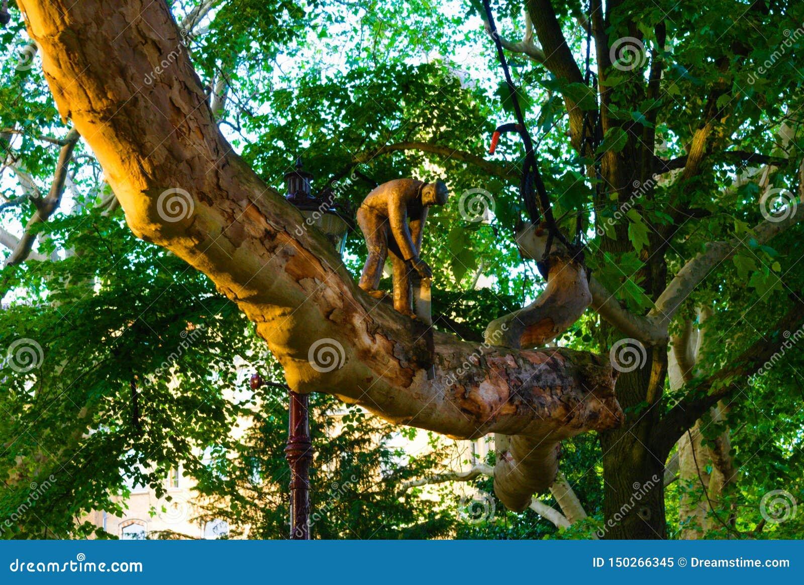 Estatueta do ferro fundido de um homem com uma serra que reduz um ramo