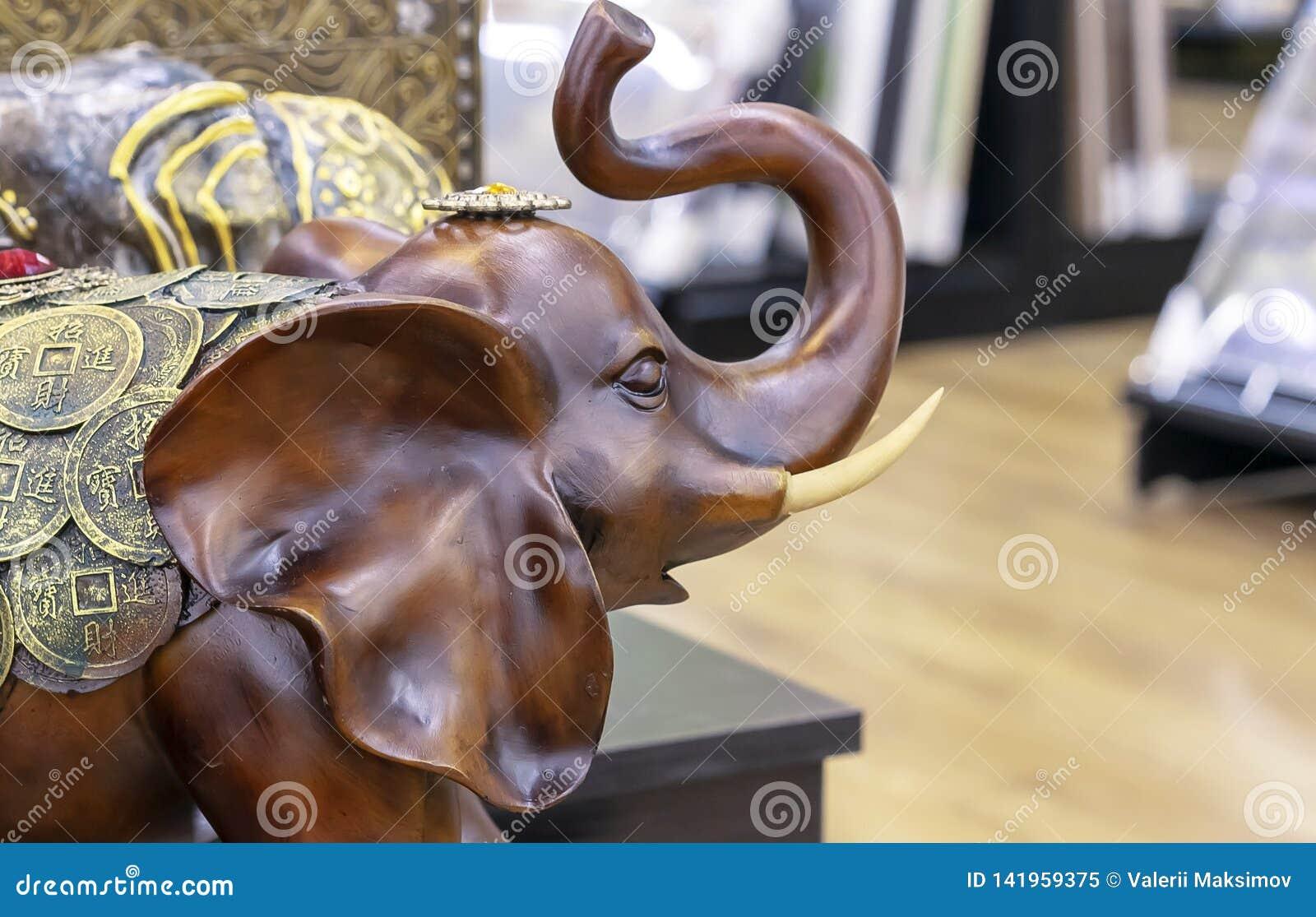 Estatuilla de madera de un elefante adornado con las monedas