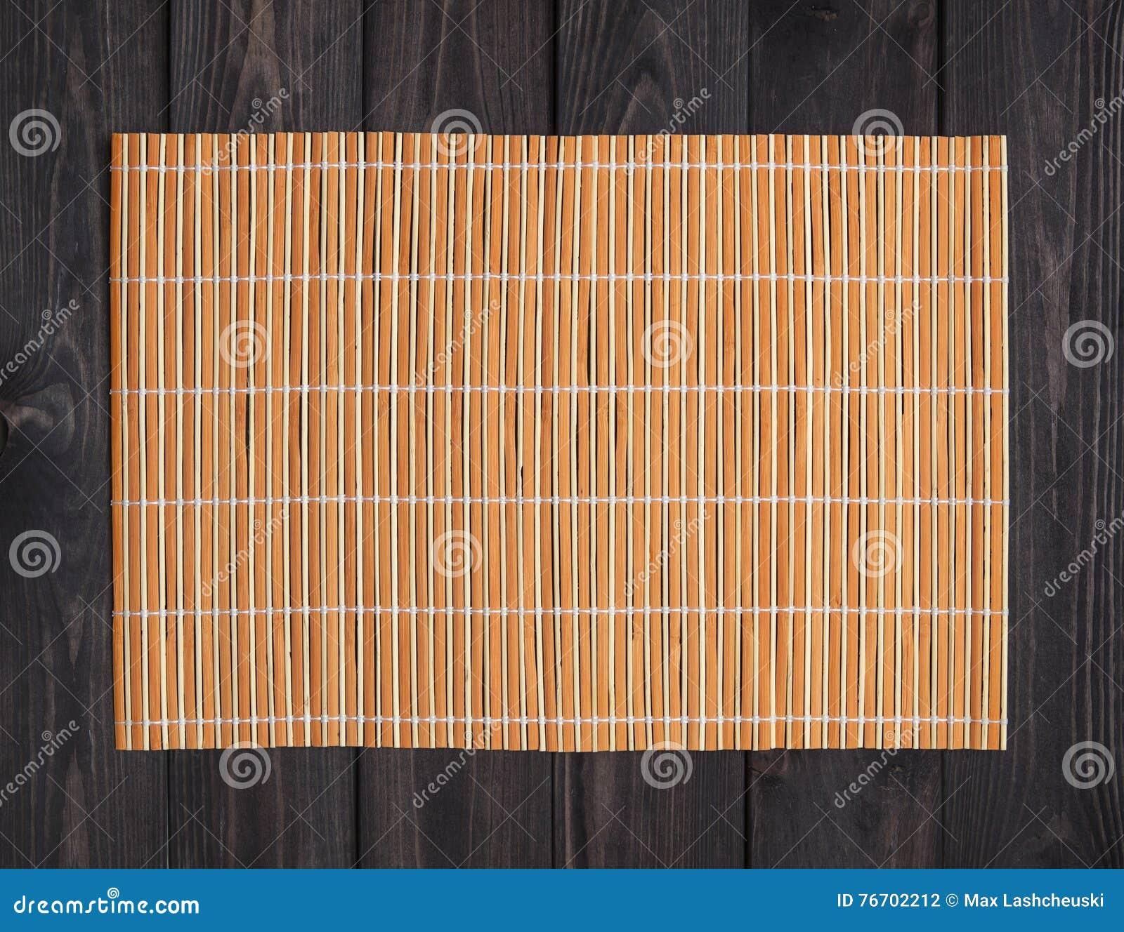 Estera de bambú en la tabla de madera, visión superior