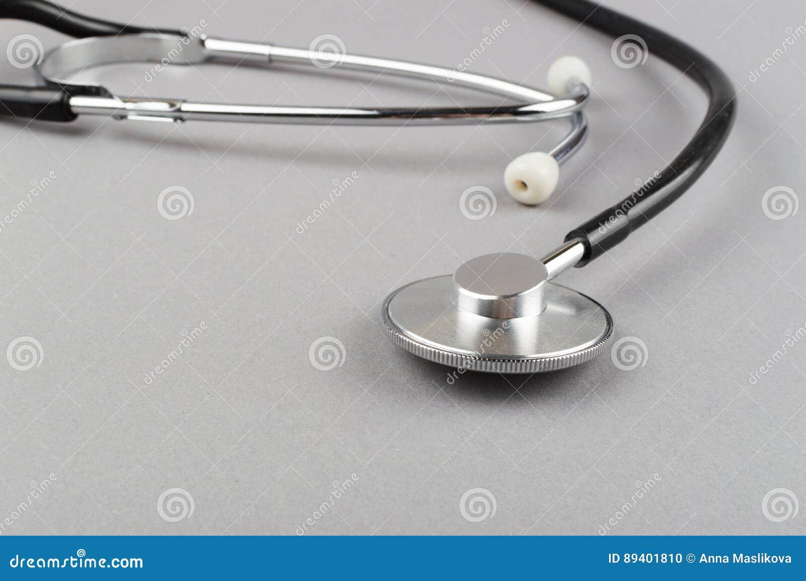 Estetoscópio - instrumento médico no fundo cinzento