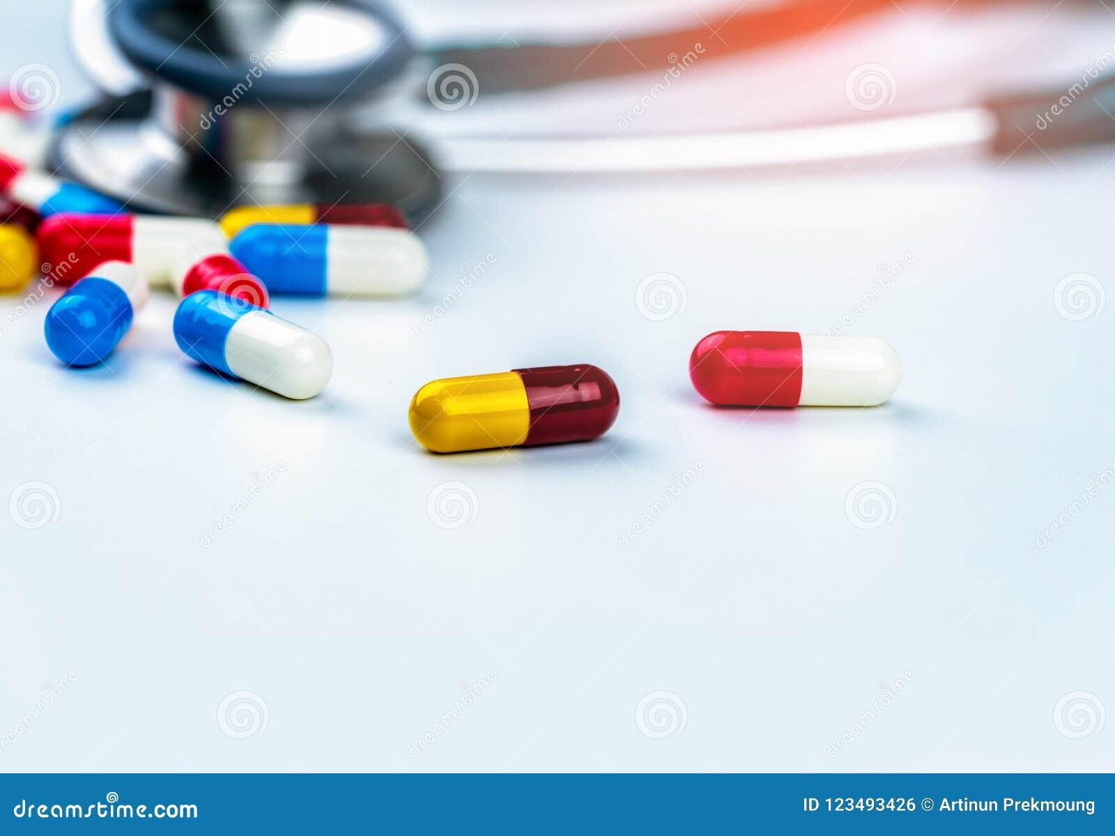 Estetoscopio con la pila de píldoras antibióticos coloridas de la cápsula en la tabla blanca Resistencia a los medicamentos y abu