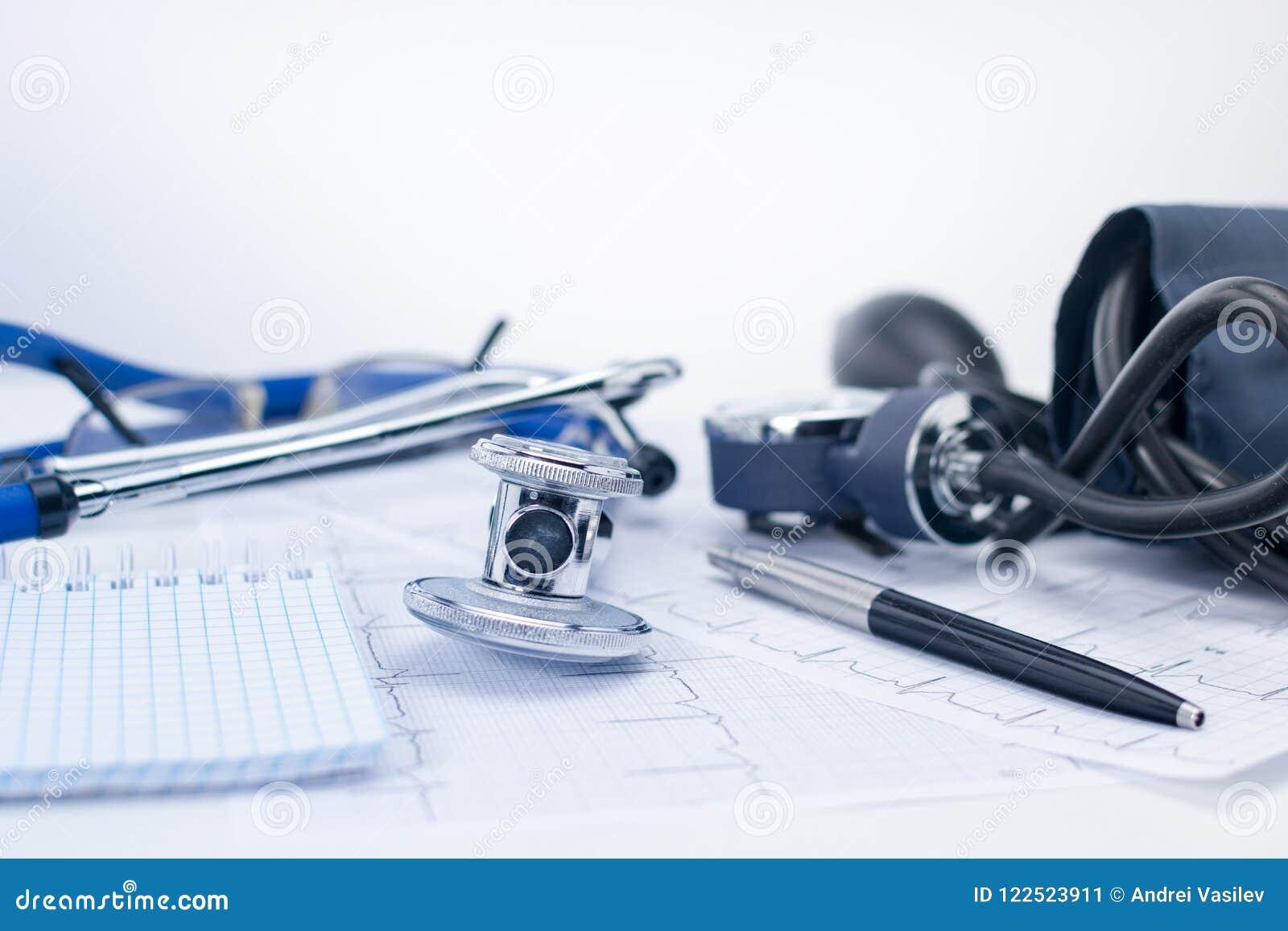 Estetoscopio en la tabla de funcionamiento de un cardiólogo Tonometer, de electrocardiograma y de libreta con el phonendoscope, m