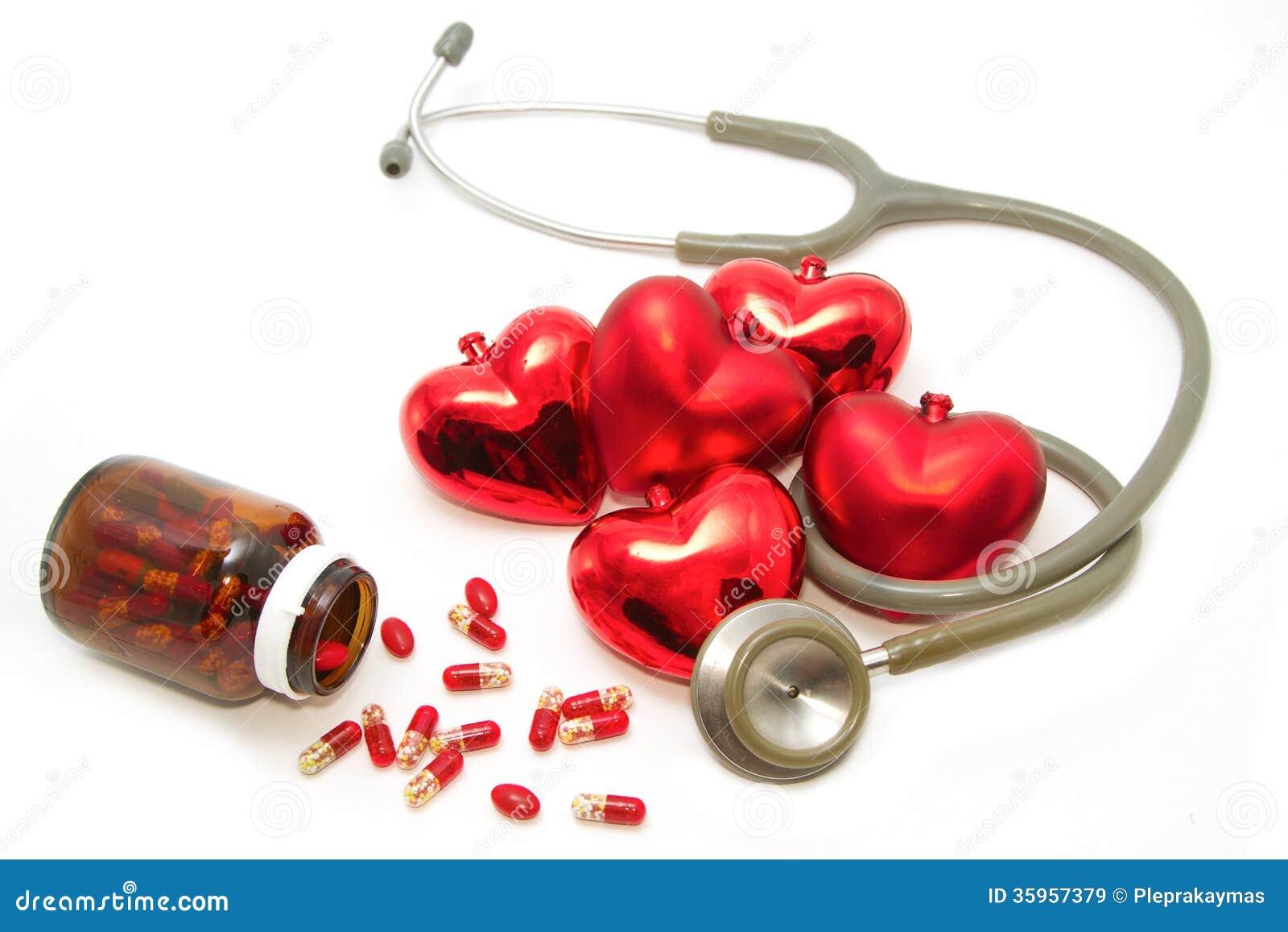 Estetoscopio que escucha el corazón y las píldoras rojos