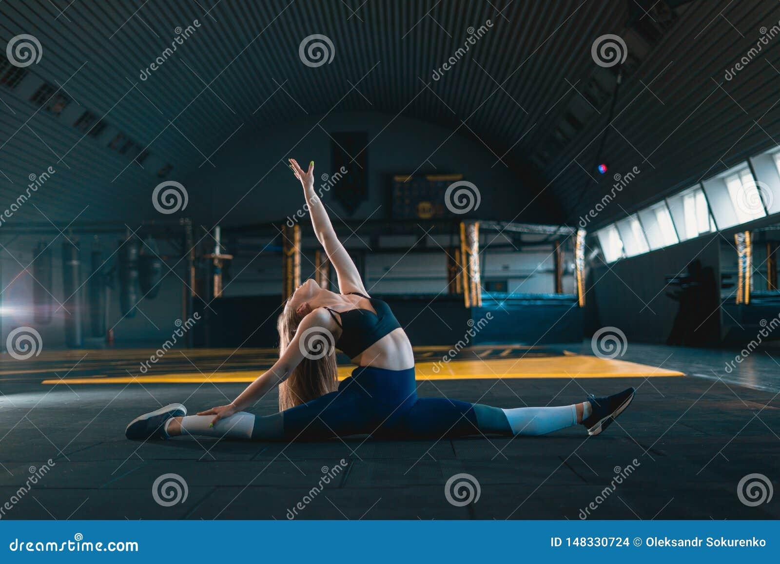 Esticando a menina da ginasta que faz a separa??o vertical, guita Opini?o lateral a jovem mulher atrativa que faz o exerc?cio do