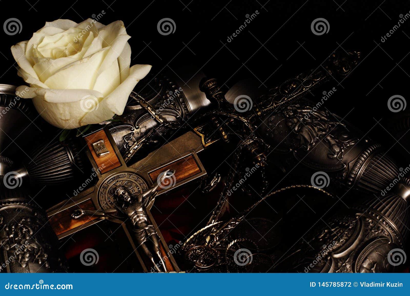 Estilete, crucifijo con la cadena integrada del metal, cubiletes del metal para el vino y rosa blanca en fondo negro Recuerdos de