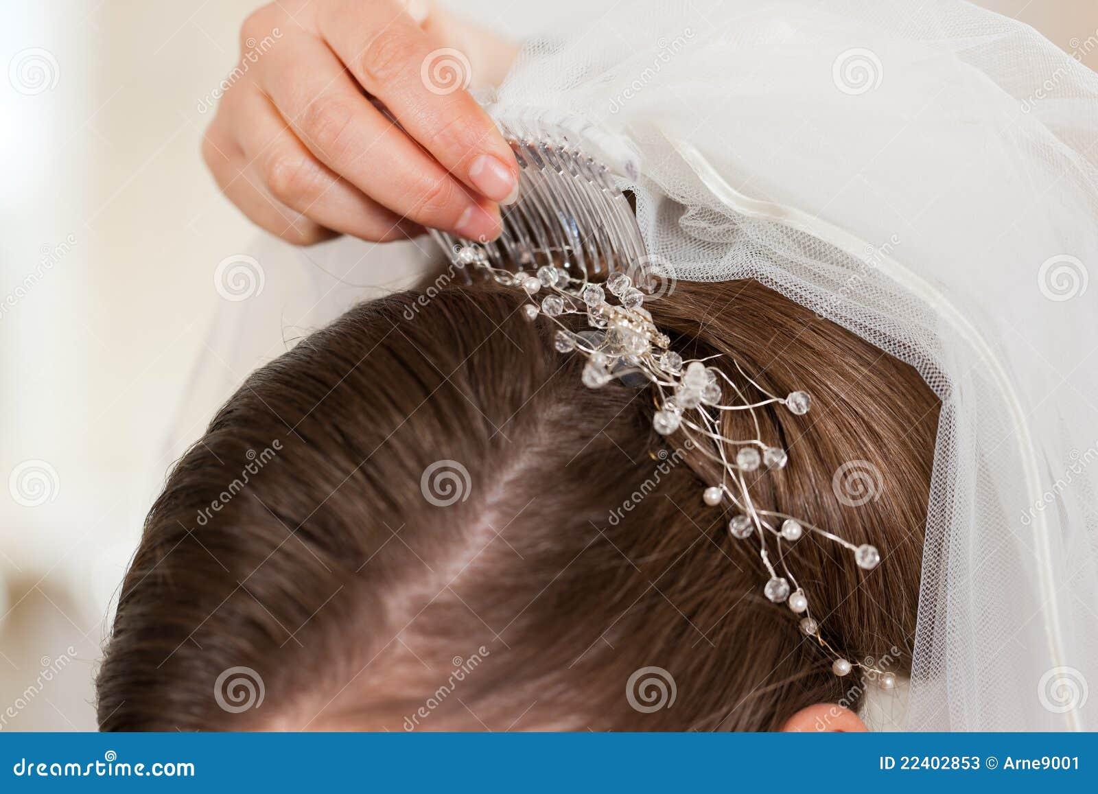 Estilista que fixa acima do penteado de uma noiva