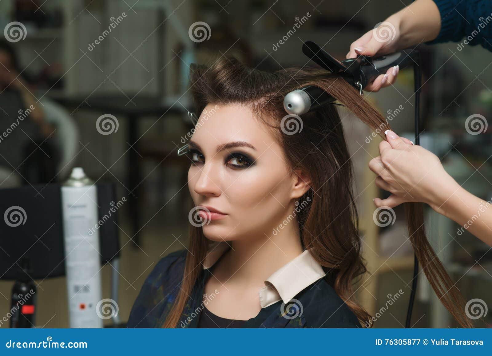 Estilista que hace rizos a la mujer morena Trabajo del peluquero
