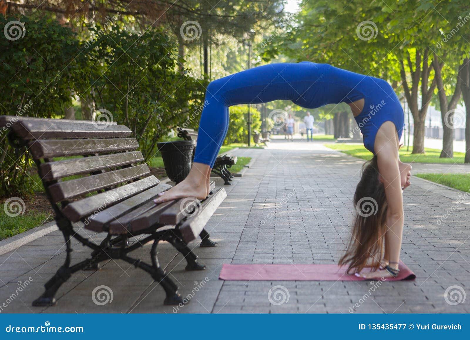 Estilo de vida saudável na natureza, mulher que faz o exercício da ioga na esteira no parque