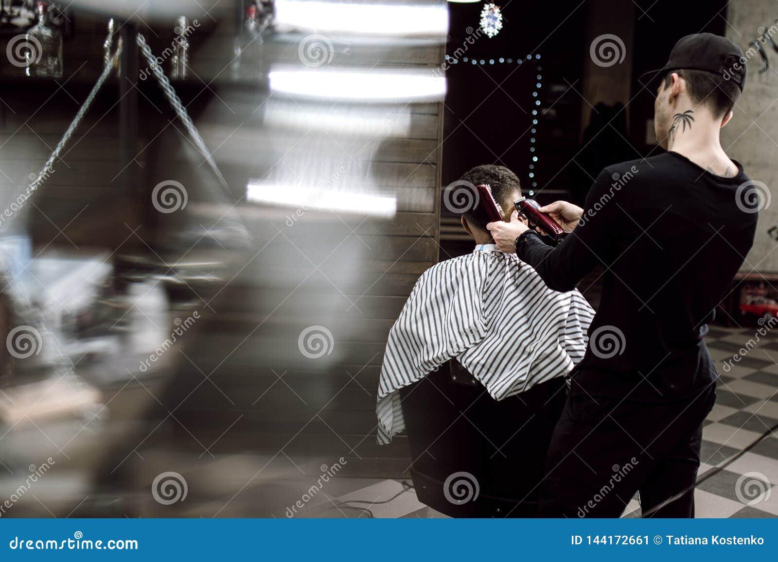 Estilo del ` s de los hombres El peluquero de la moda hace un peinado elegante para un hombre negro-cabelludo que se sienta en la