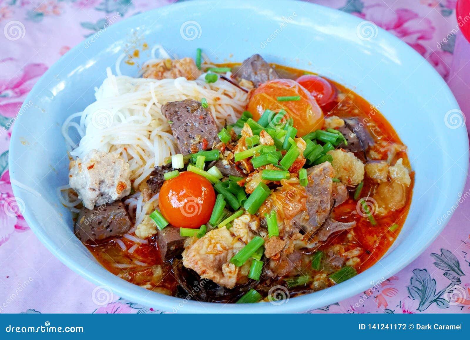 Estilo tailandês do alimento, macarronetes de arroz com molho picante da carne de porco na bacia