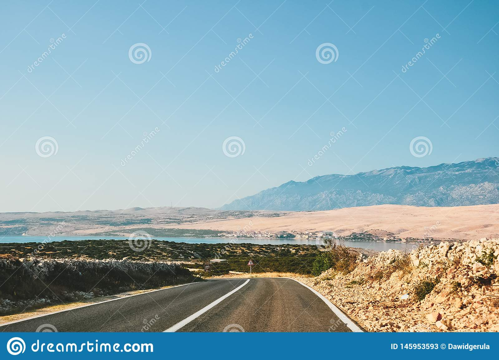 Estrada cênico pelo mar na Croácia que conduz ao Pag, na ilha, com as montanhas no fundo