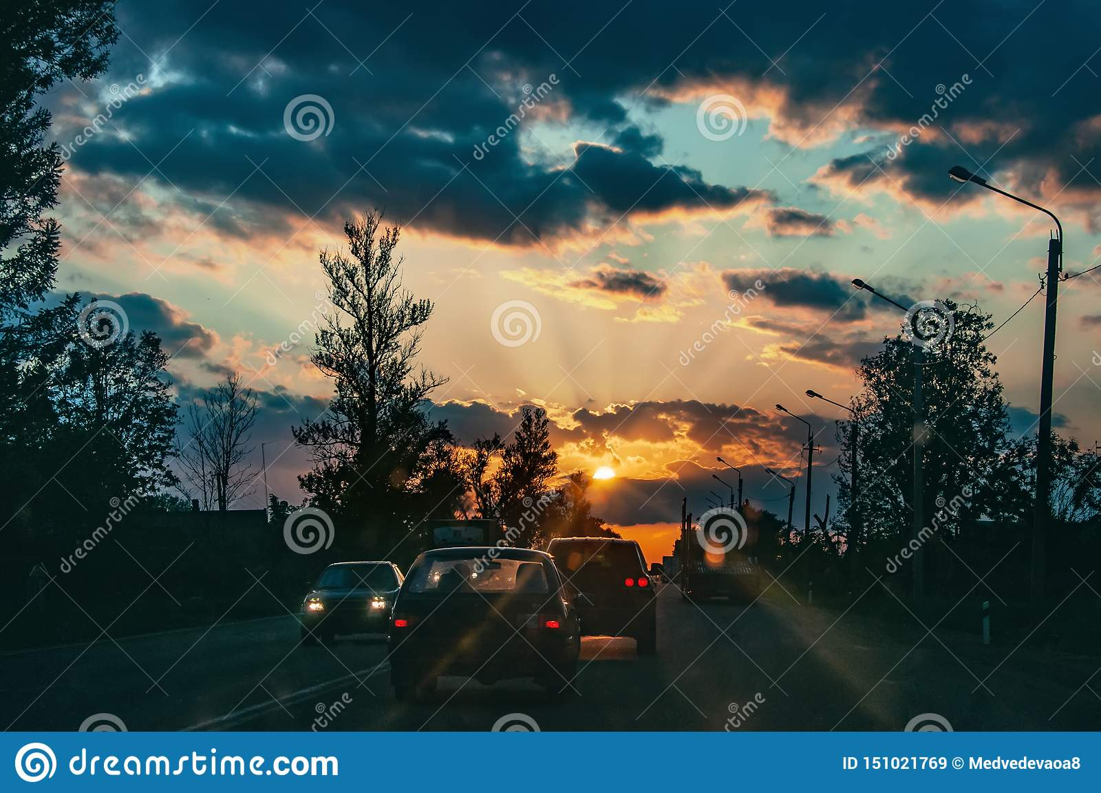 Estrada com os carros que viajam no por do sol Linha do horizonte com o sol e as nuvens de tempestade viagens Foco seletivo