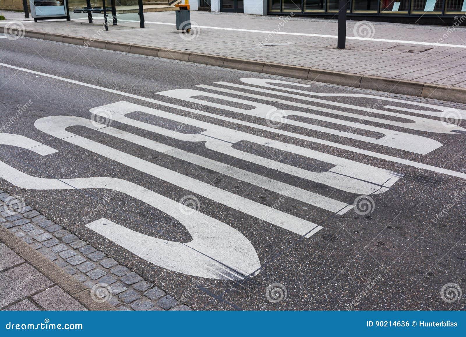 A estrada das marcações da segurança do ônibus pintada alinha o público Transportati das pistas