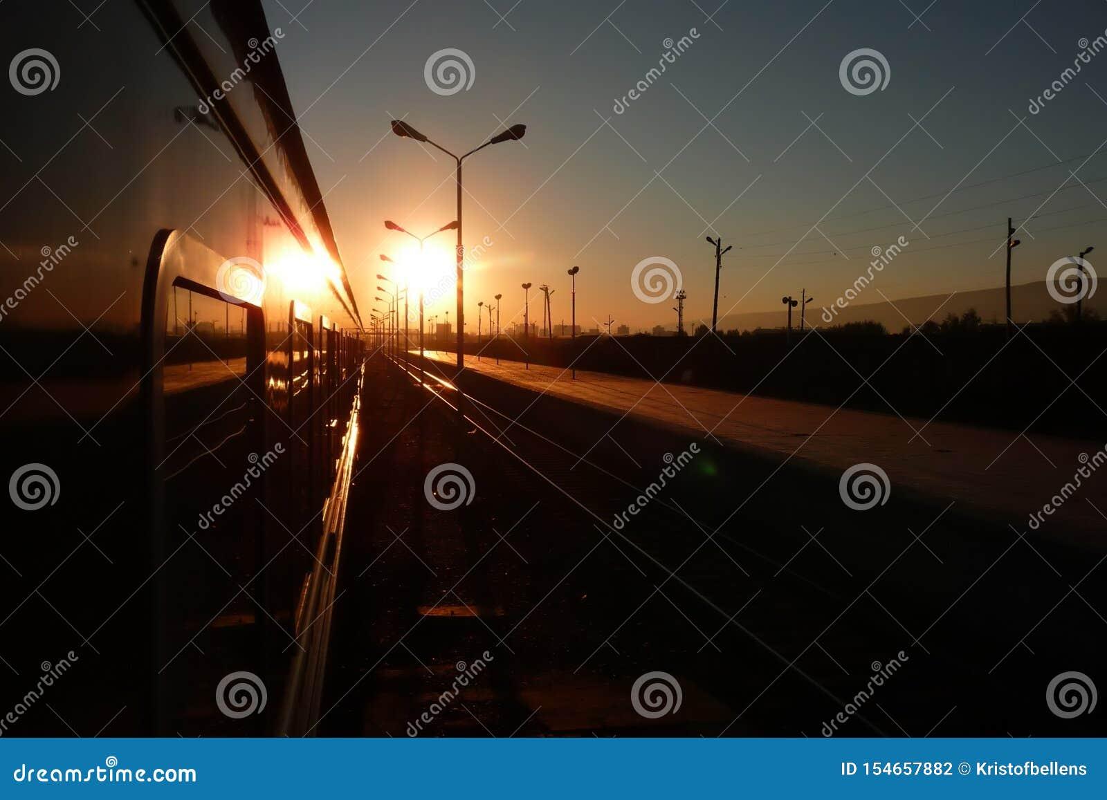 Estrada de ferro transiberiana: ideia da janela do lado do trem no nascer do sol em um estação de caminhos de ferro do russo