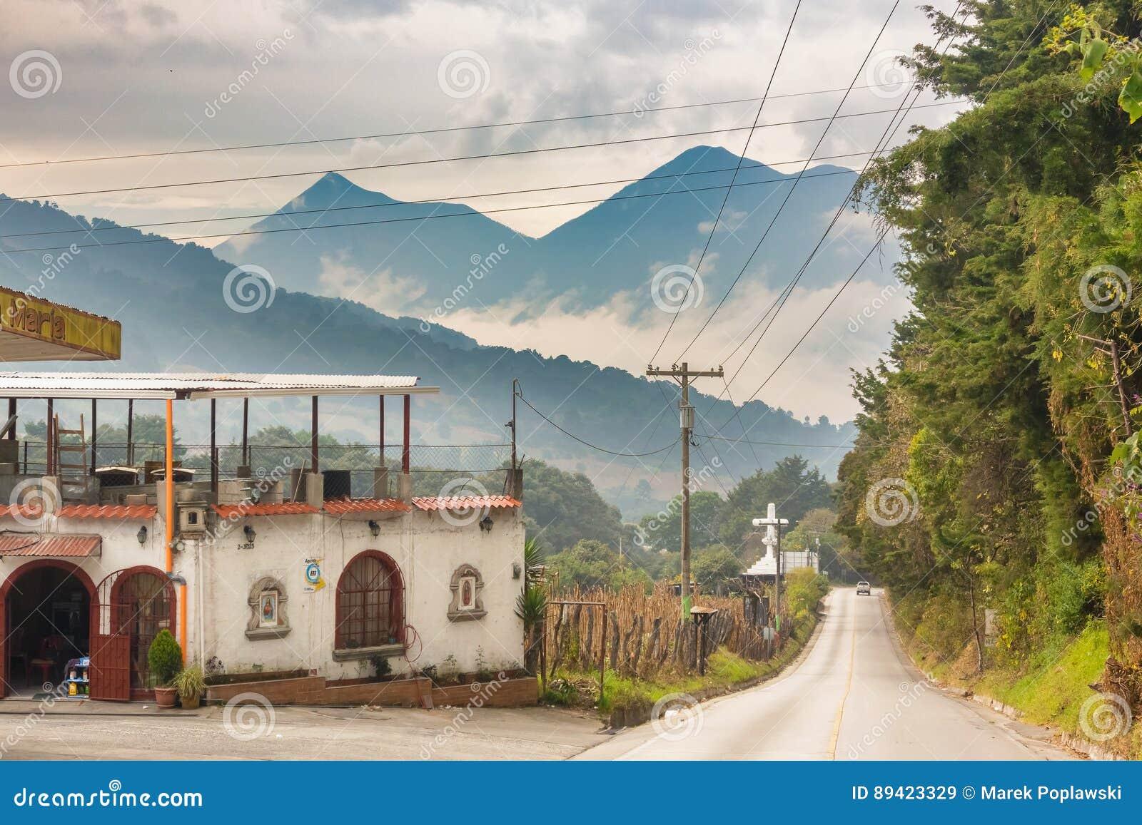 A estrada de terra e as montanhas vulcânicas ajardinam na Guatemala