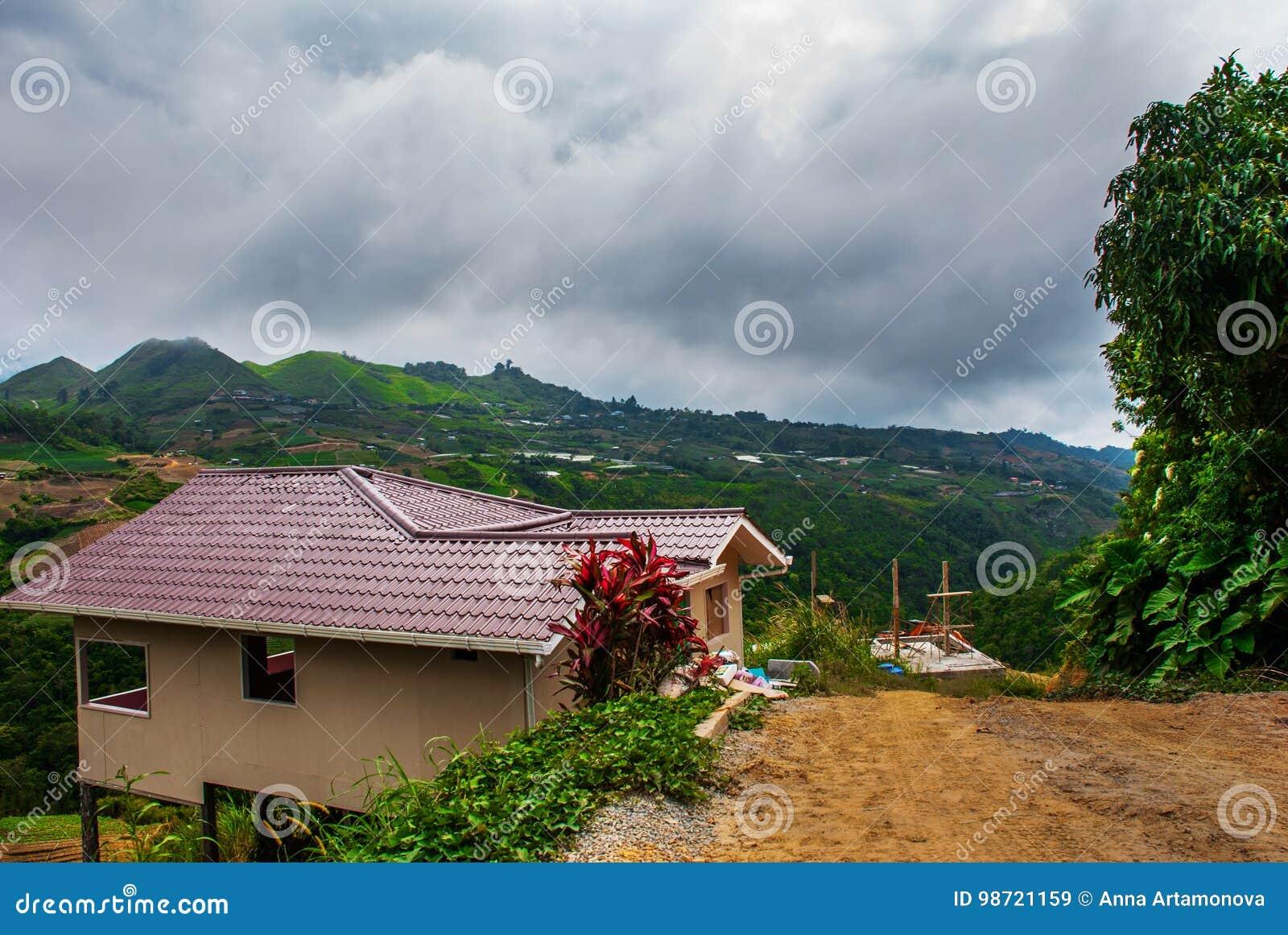 A estrada e as casas na vila nas inclinações das montanhas com nuvens Sabah, Bornéu, Malásia