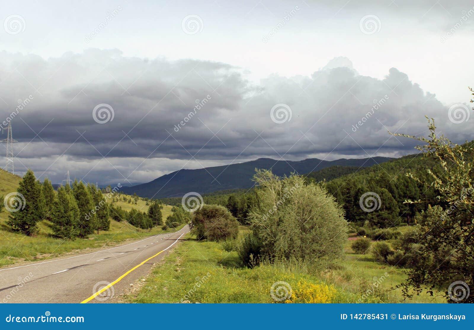 A estrada na floresta sob um céu azul com branco nubla-se montanhas de Sayan Sibéria Rússia