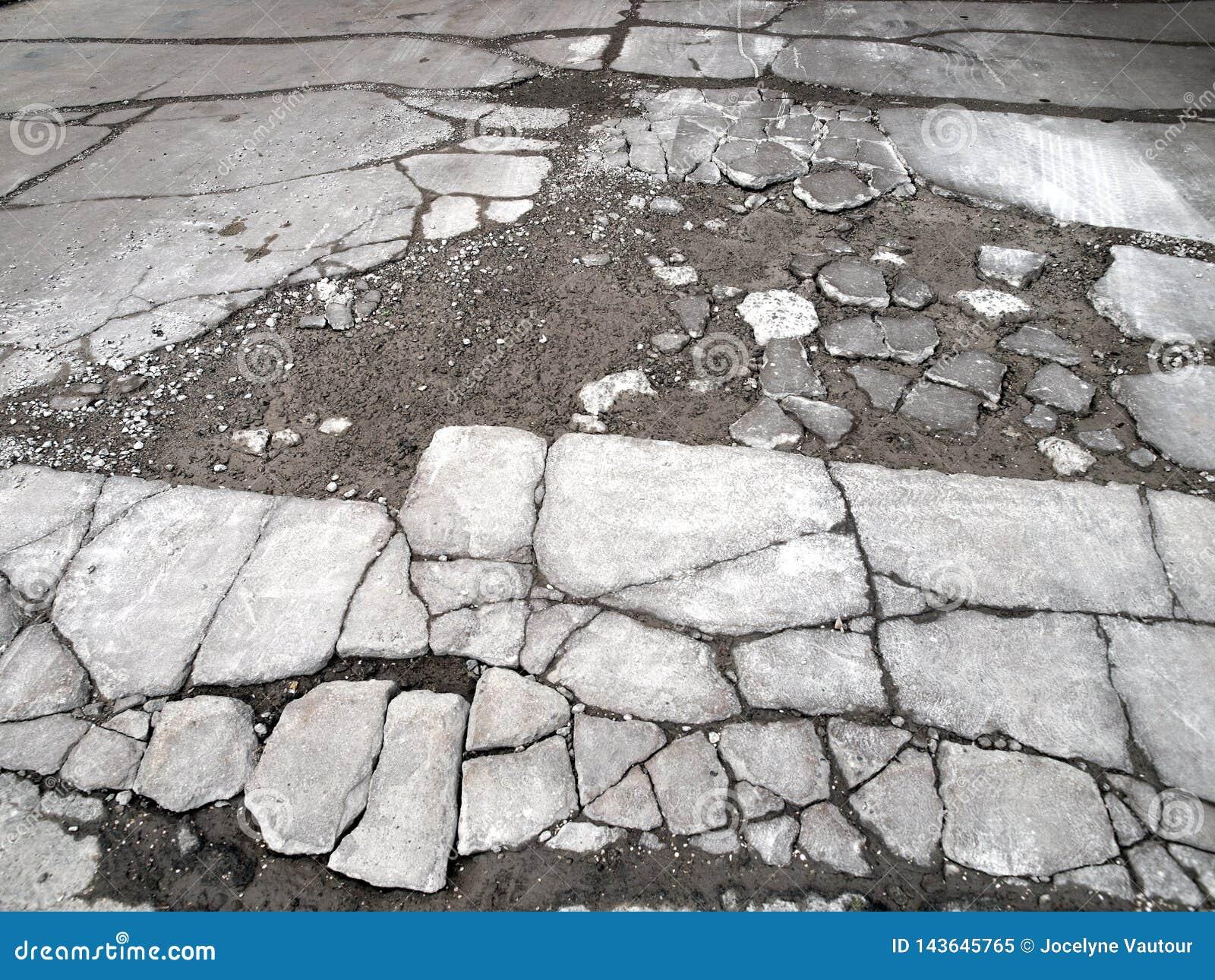 Estrada pavimentada deteriorando-se e rachada