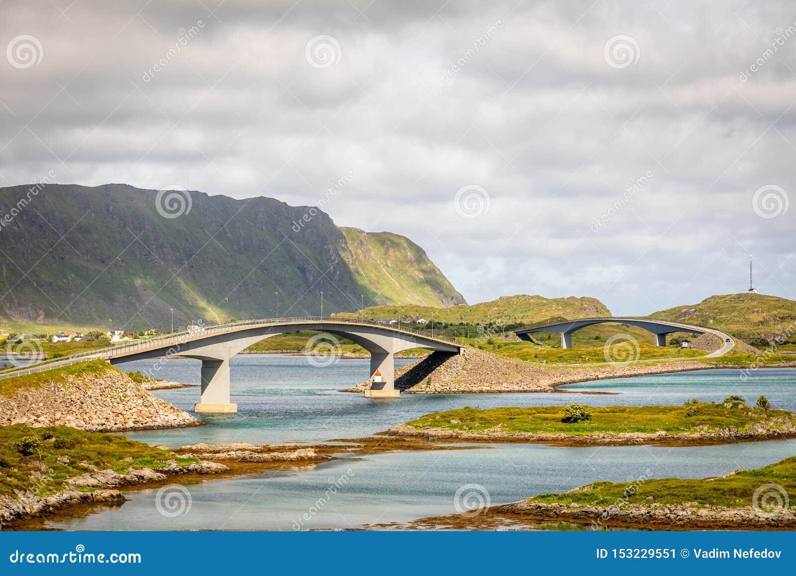 Estrada torcida da estrada com as pontes de Freedvang no fiorde, ilha de Lofoten, condado de Nordland da municipalidade de Flakst