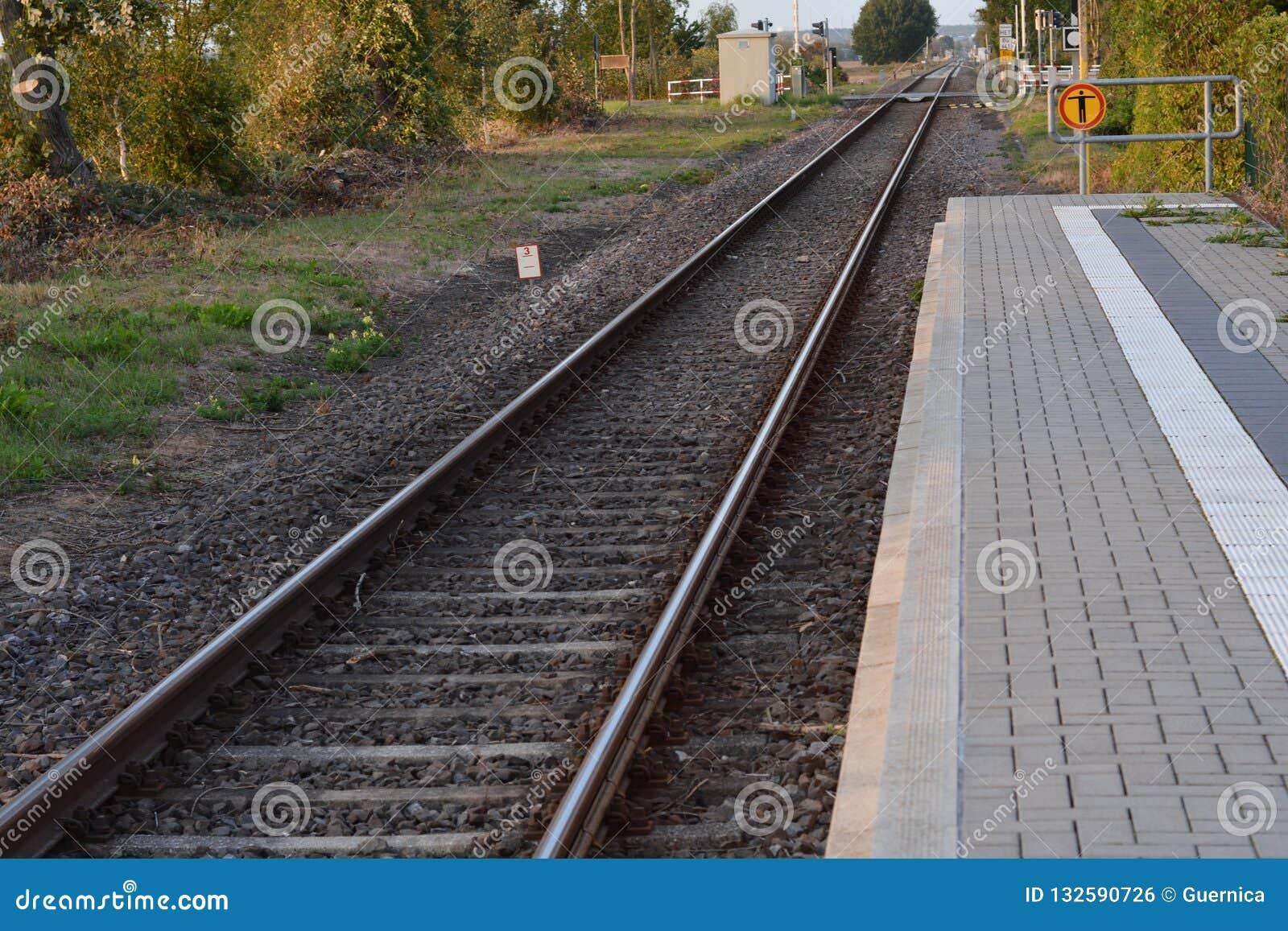 Estradas de ferro vazias no fundo do céu do por do sol