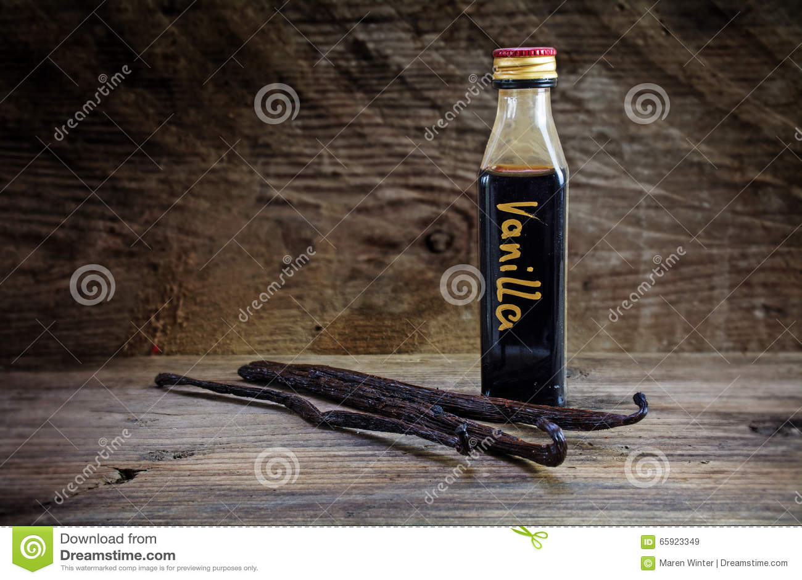 Estratto di vaniglia, casalingo in una piccola bottiglia e nei baccelli di vaniglia sopra