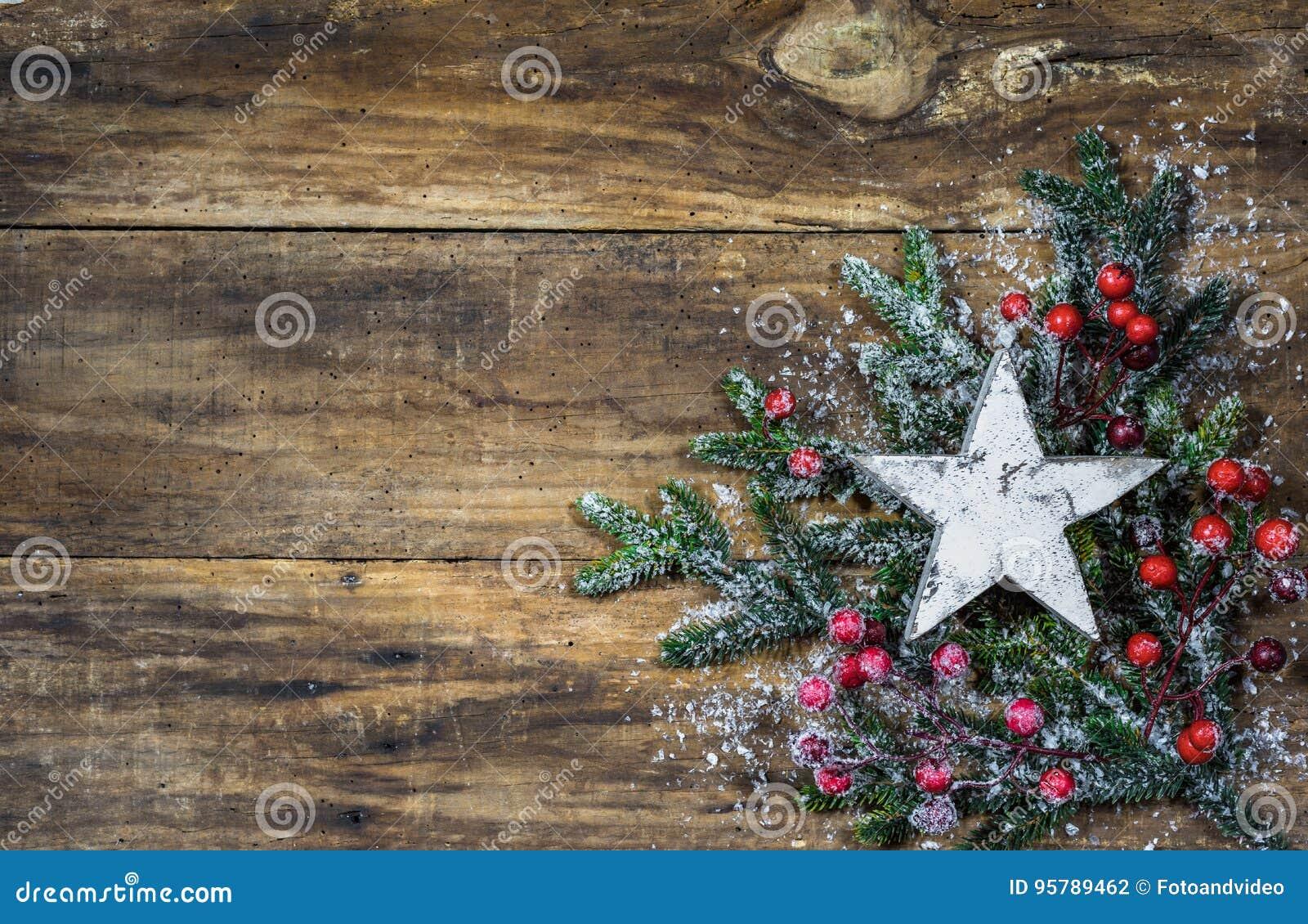 Estrela do Natal em ramos de árvore do abeto e na decoração vermelha das bagas