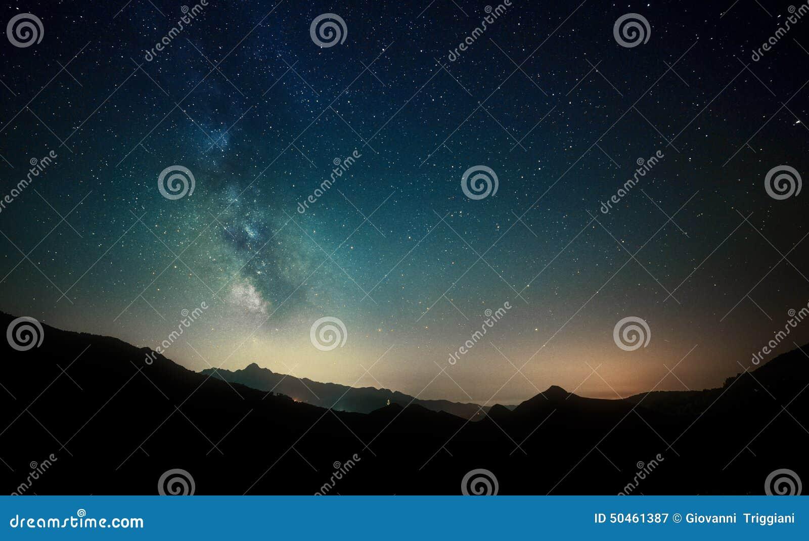 Estrelas do céu noturno com Via Látea no fundo da montanha