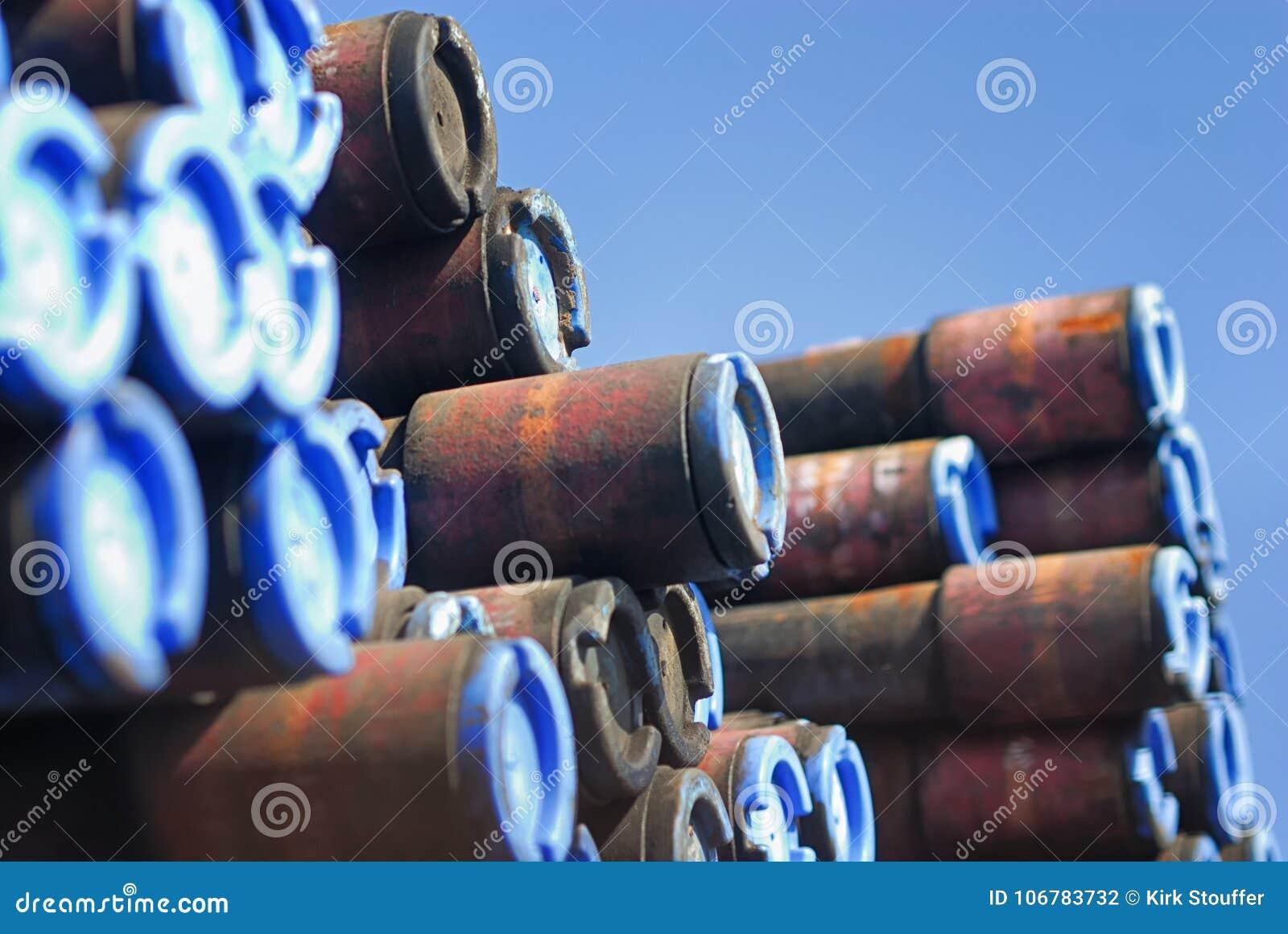 Estremità di una pila di tubi coperti di cappucci blu