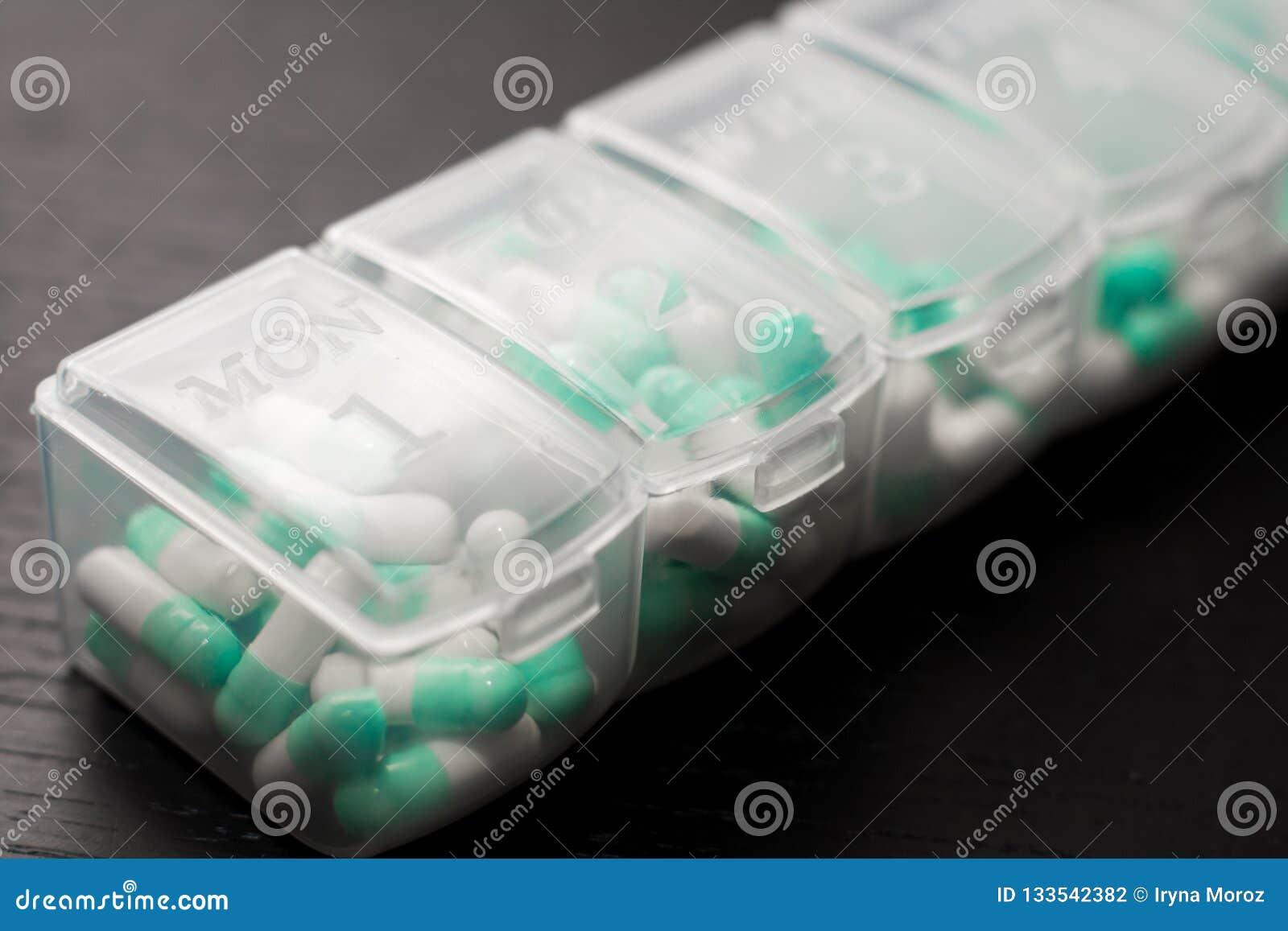 Estremo vicino su della scatola di sette giorni della pillola con le pillole Pillola-scatola blu