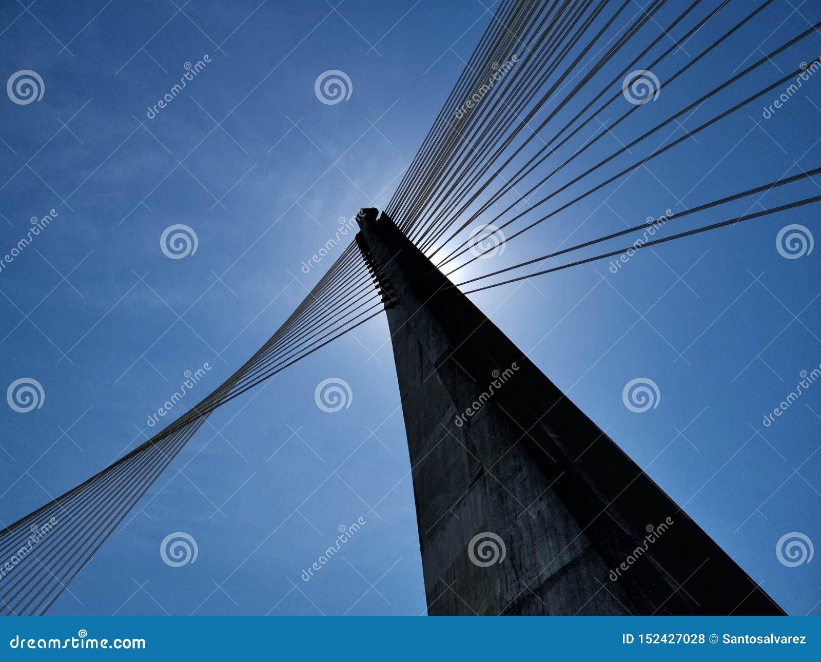 Estructura concreta con los apoyos de acero de un puente sobre un río debajo de un cielo azul intenso
