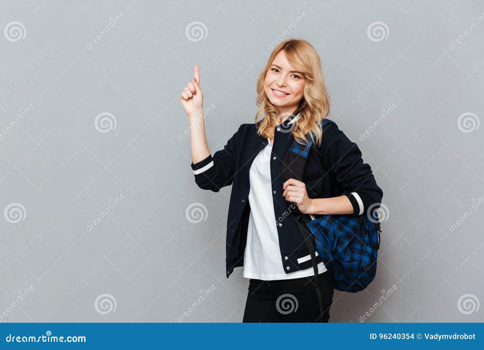 Estudante alegre da jovem senhora com apontar da trouxa