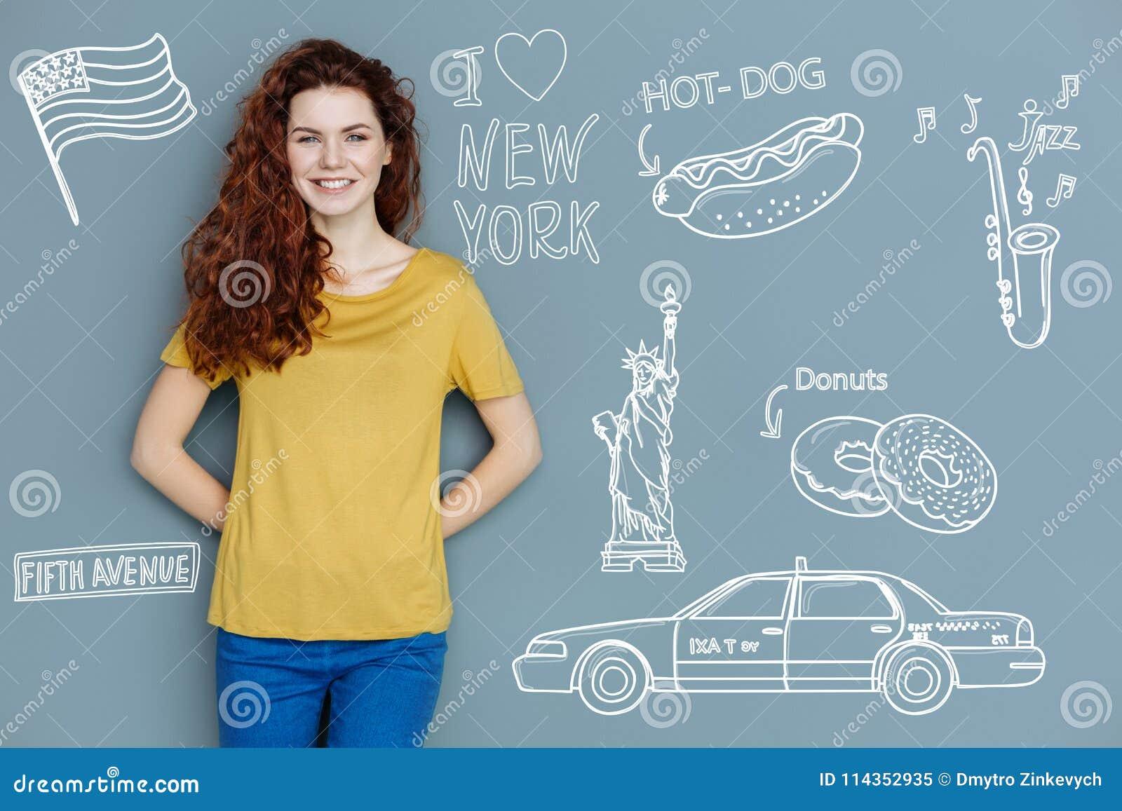 Estudante alegre que sorri ao sonhar sobre a viagem a New York